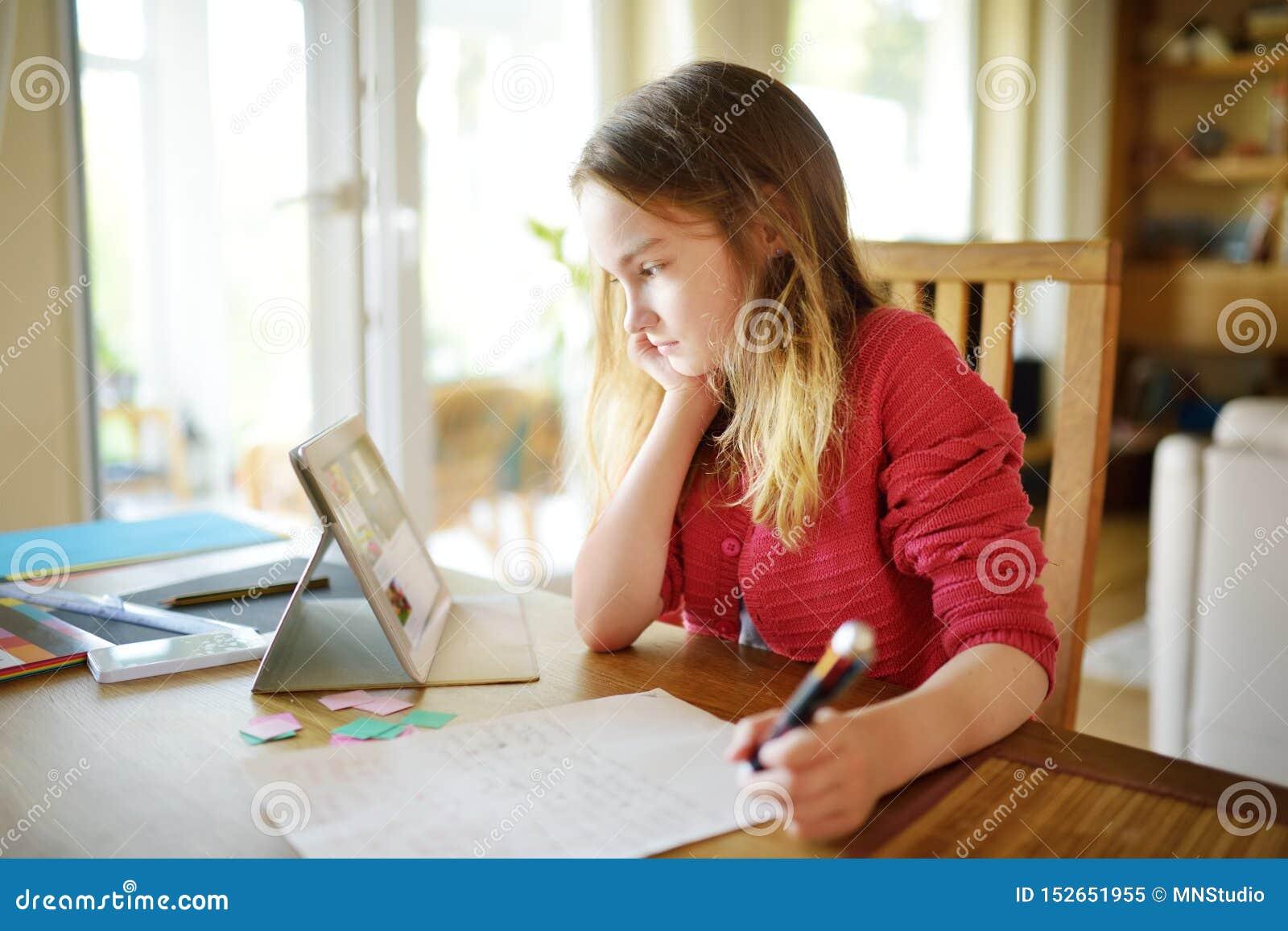 Scolara preteen astuta che fa il suo compito con la compressa digitale a casa Bambino facendo uso degli aggeggi da studiare