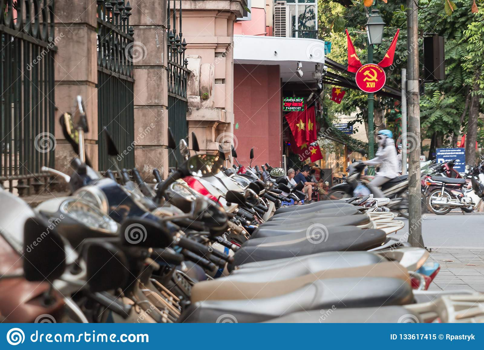 Scooters and communist propaganda symbol in Hanoi, Vietnam