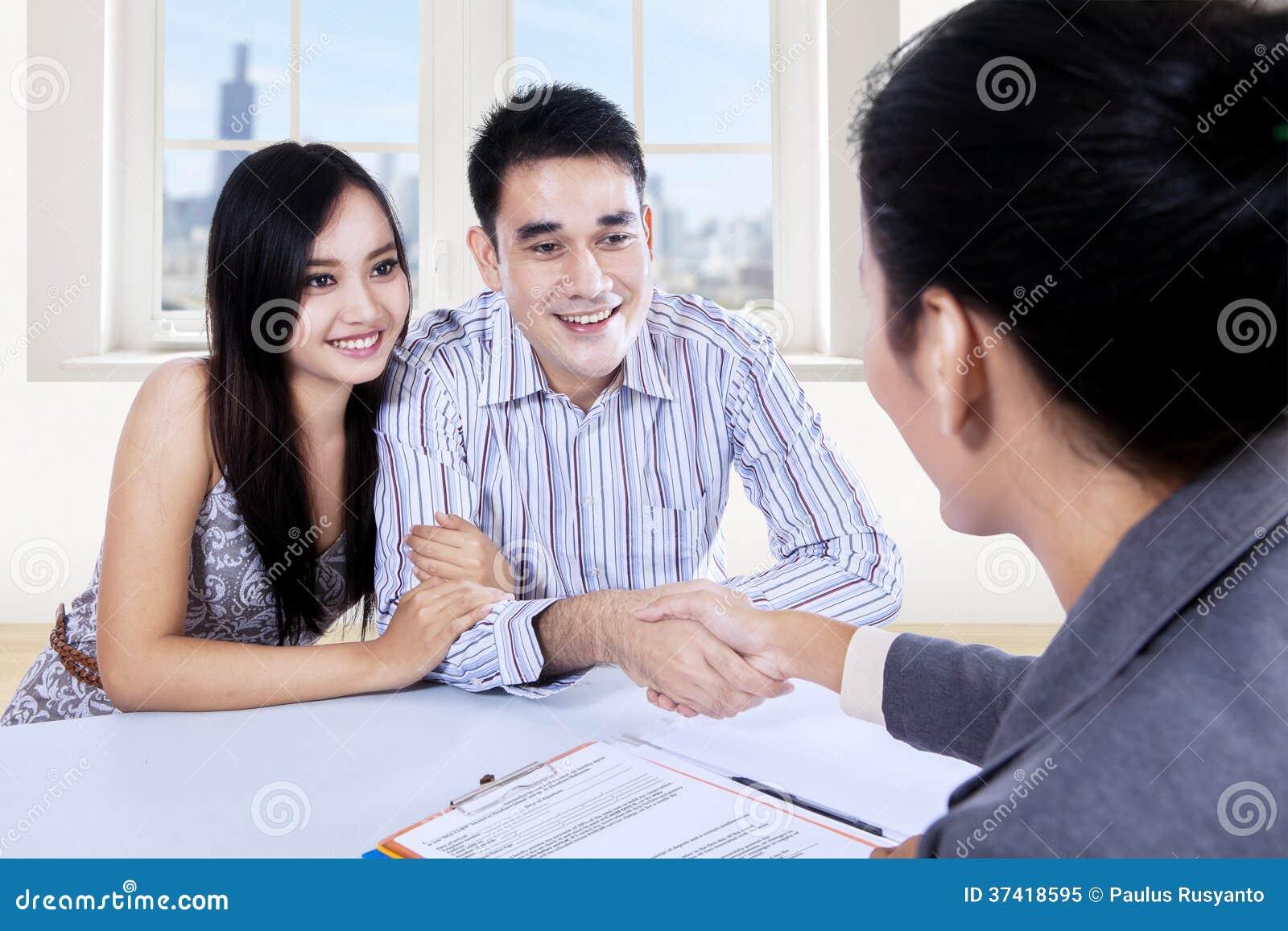 Scossa asiatica della mano delle coppie con la donna di affari