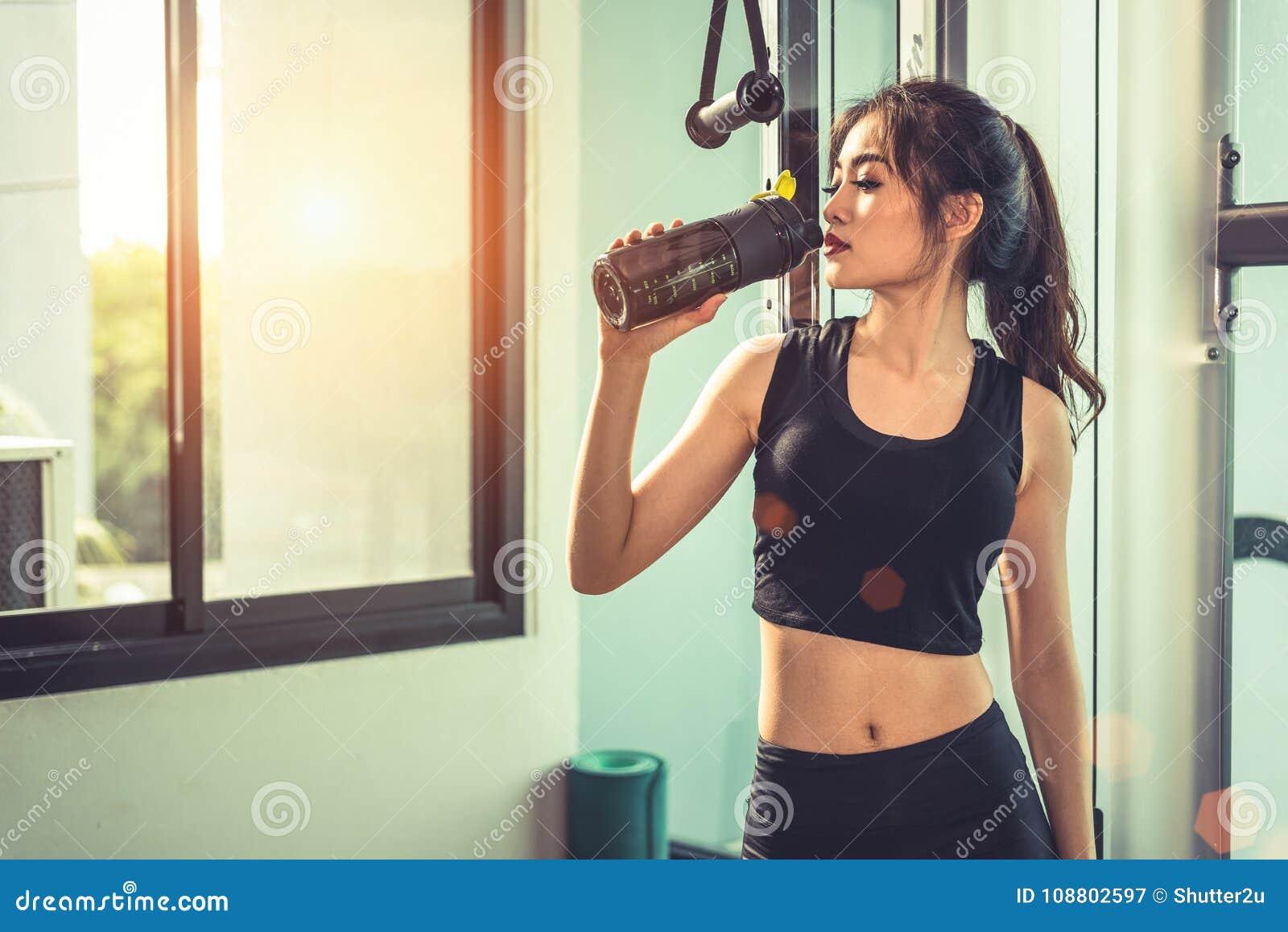 Scossa bevente o acqua della proteina della giovane donna asiatica dopo l esercizio
