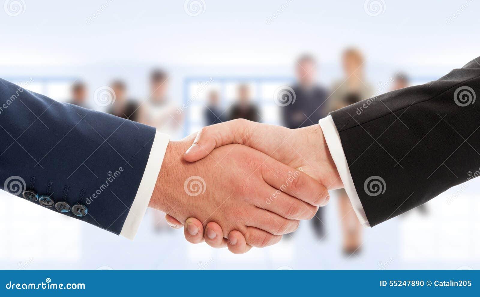 Scossa della mano degli uomini d affari con la gente di affari nel fondo