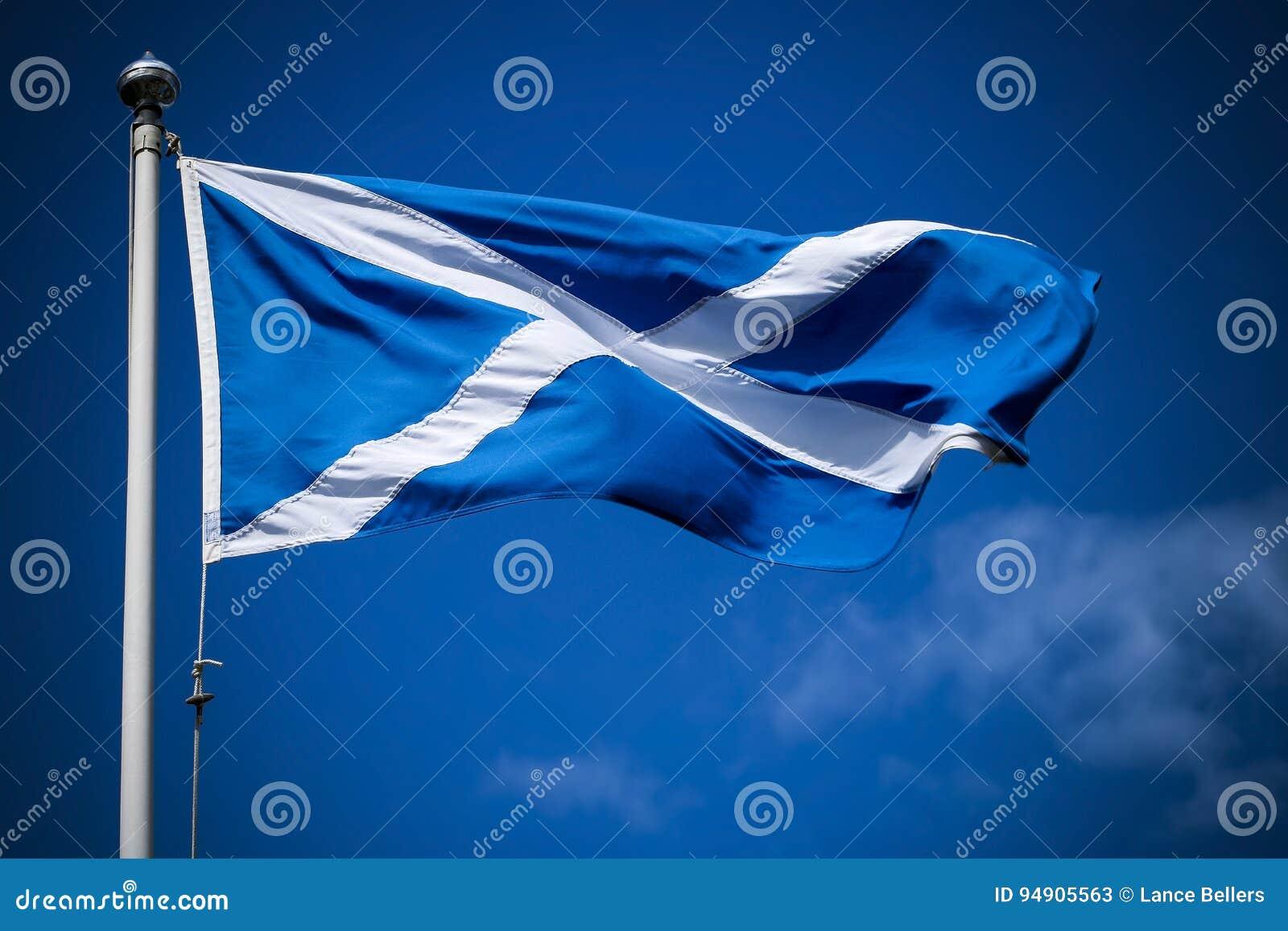 Scotland flag flying in sunshine against blue sky
