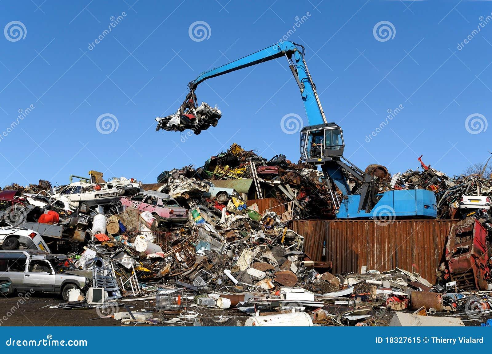 Scrapyard scenery - special car is dividing metal rubbish.