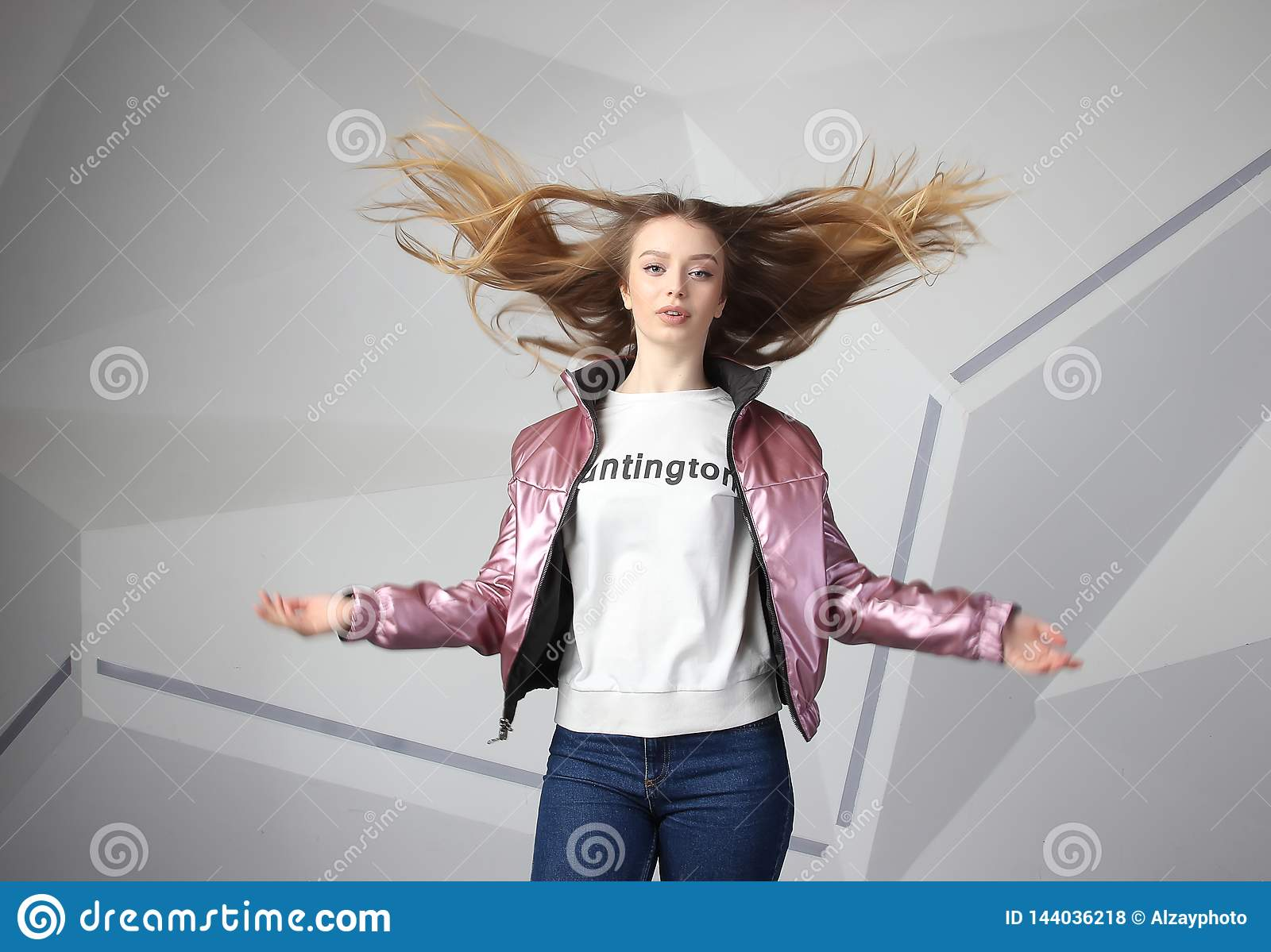 Screaming furious aggressive brunette woman with flying long hairs, flash studio portrait on modern wall
