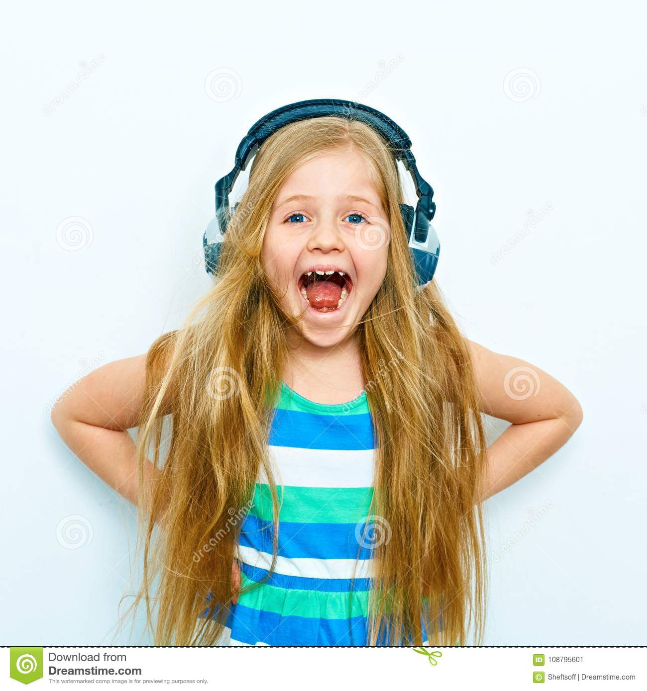 Screaming little girl with headphones funny portrait isolated o