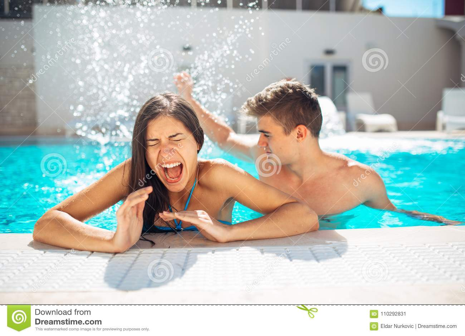 Screaming young teenage girl at the pool annoyed with pool splashing.Splashing water and playing games at the pool,having fun