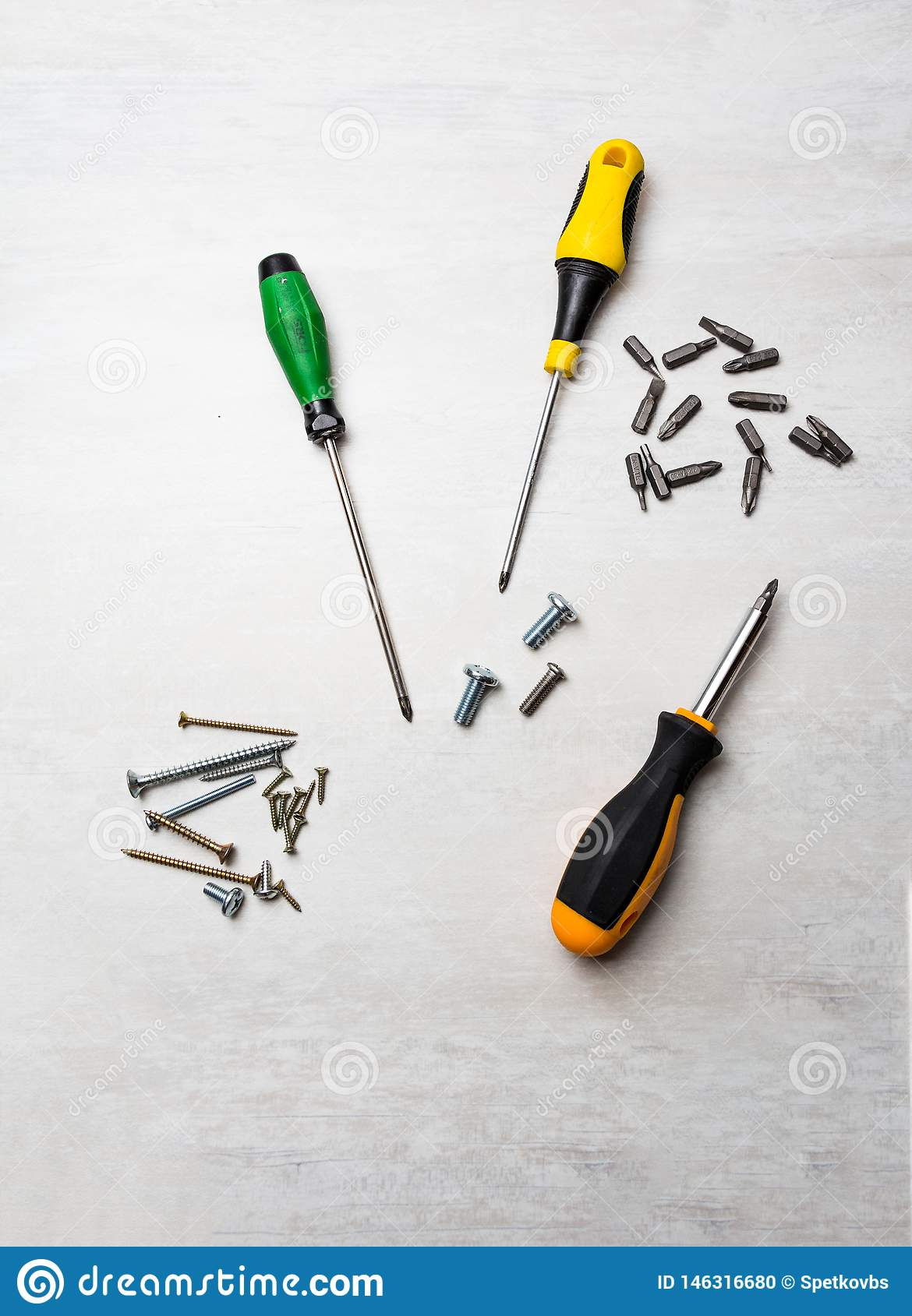 Screwdrivers and bits on desk background