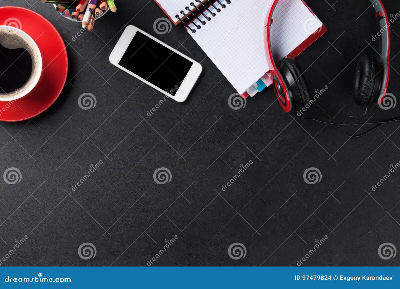 Scrittorio con il blocco note, il caffè, lo smartphone e le cuffie