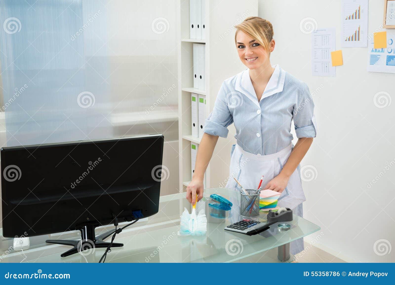Scrittorio di pulizia della domestica in ufficio
