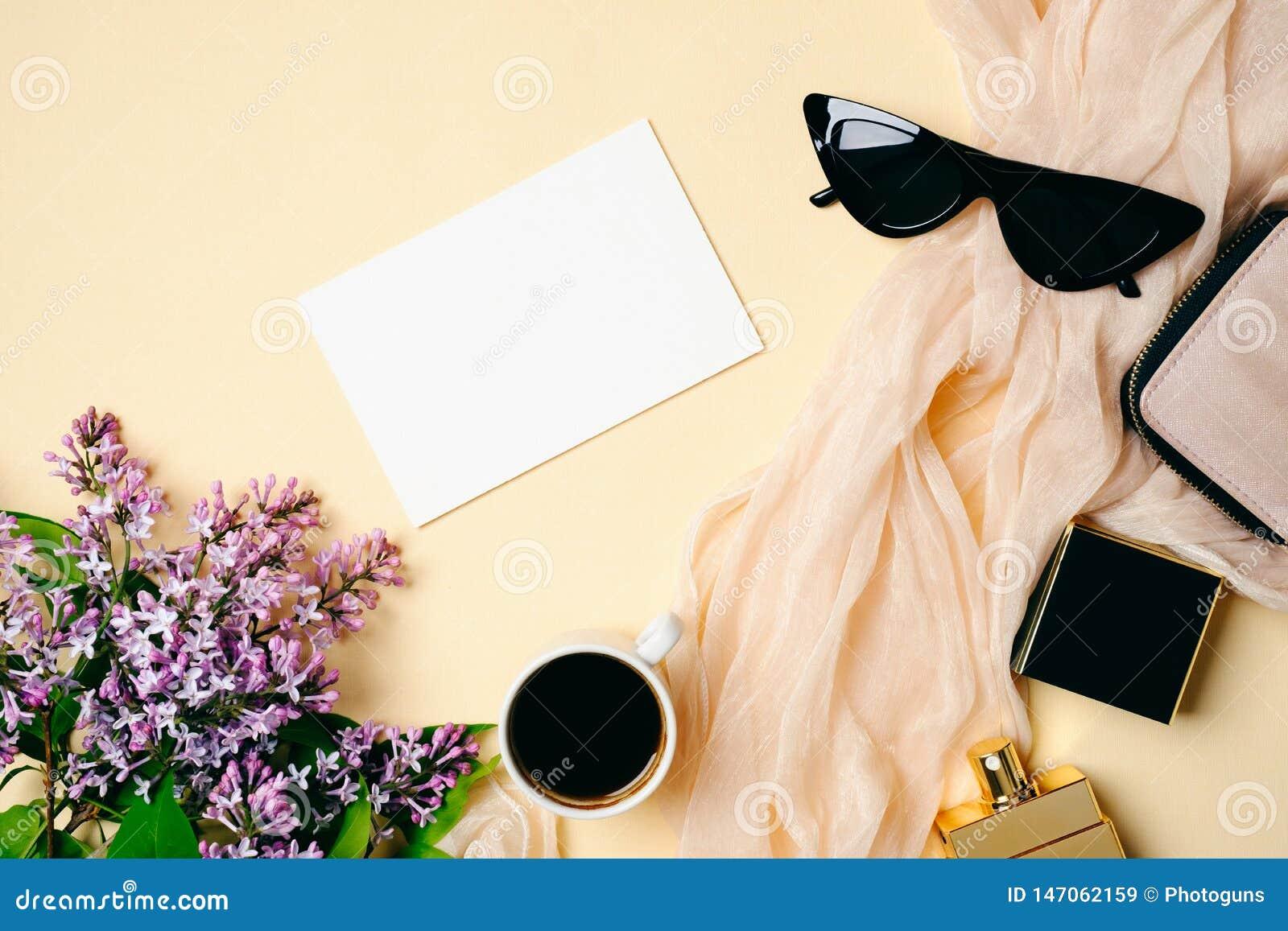 Scrittorio femminile con la carta di Libro Bianco, la sciarpa di seta, la bottiglia di profumo, la tazza di caffè, gli occhiali d