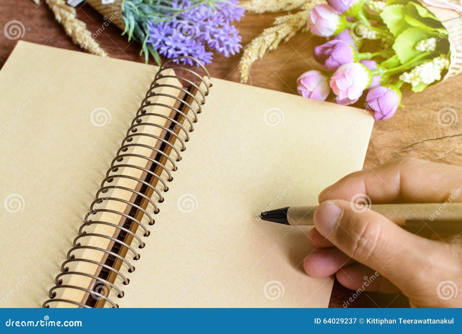 Scrittura della mano e del fiore sul taccuino in bianco sulla tavola di legno