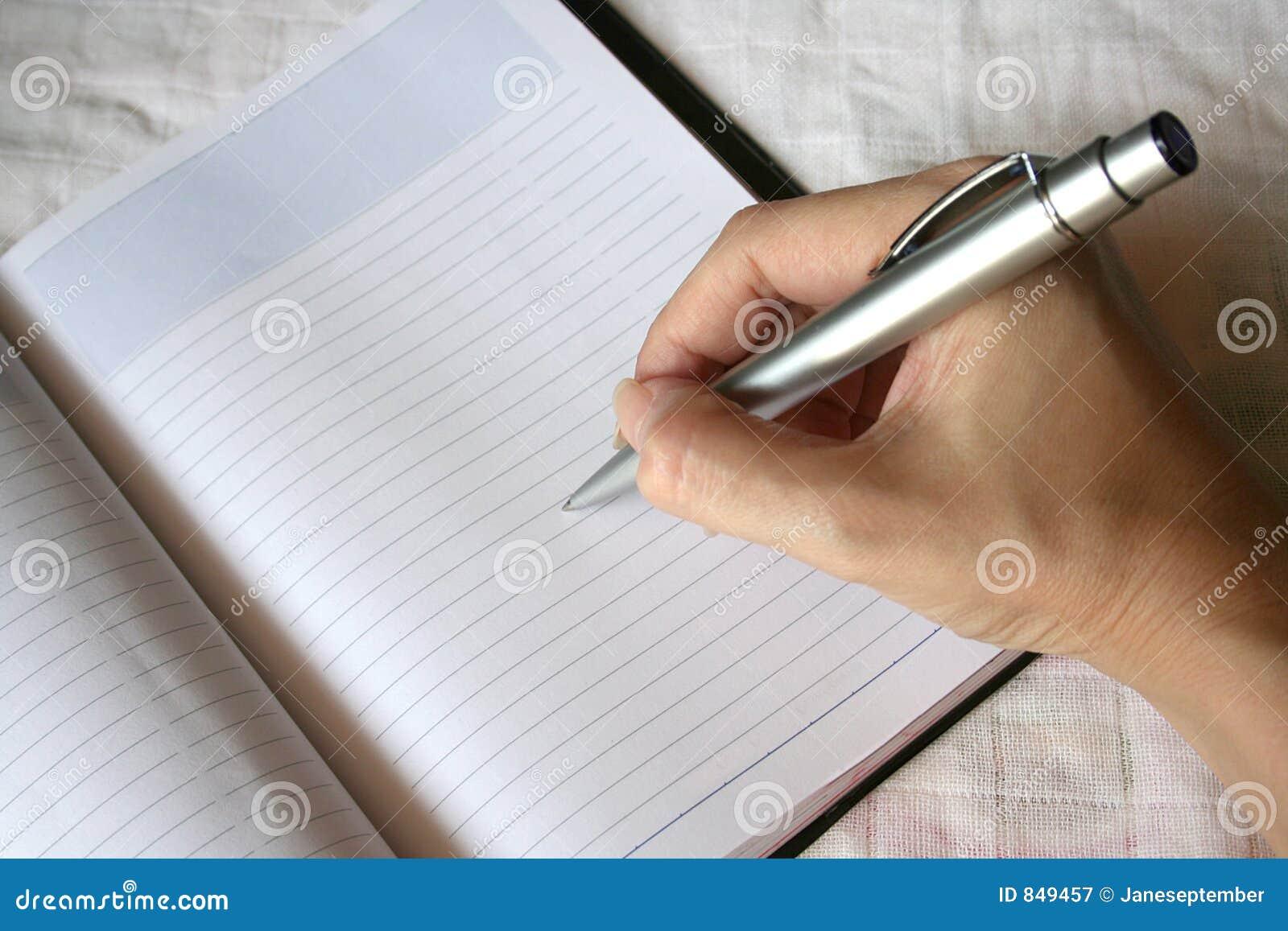 Scrittura della penna di holding della mano sul taccuino
