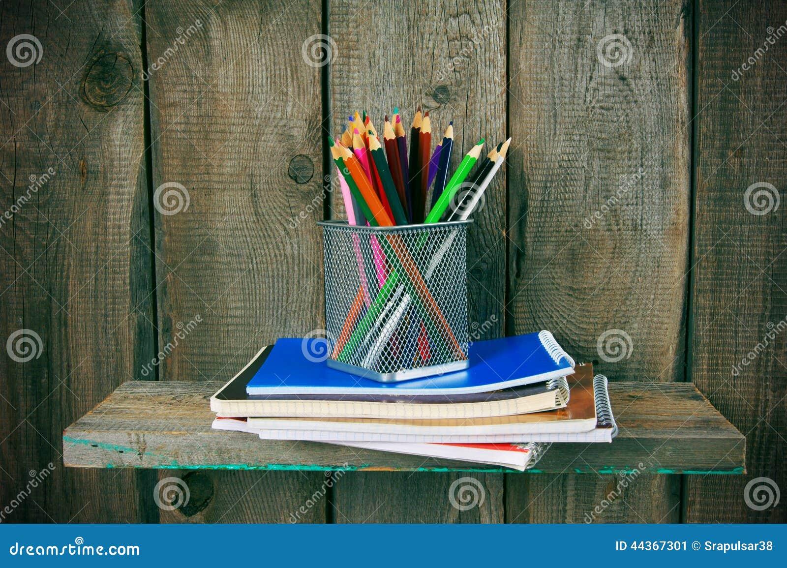 Scrittura-libri e strumenti della scuola su uno scaffale di legno