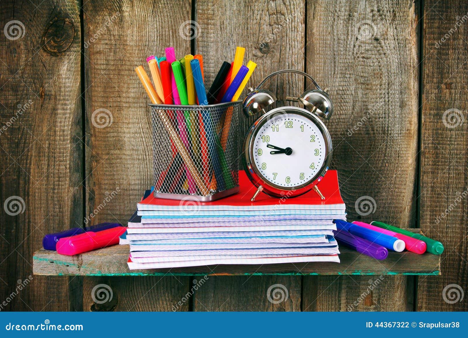 Scrittura-libri, una sveglia e strumenti della scuola