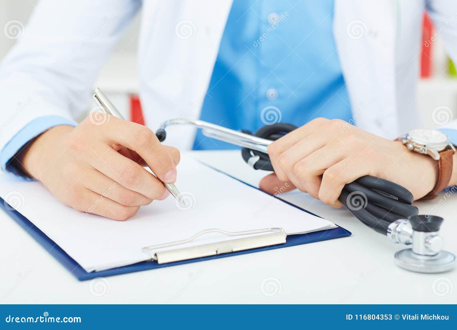 Scrittura maschio della penna dell argento della tenuta della mano di medico della medicina qualcosa sul primo piano della lavagn