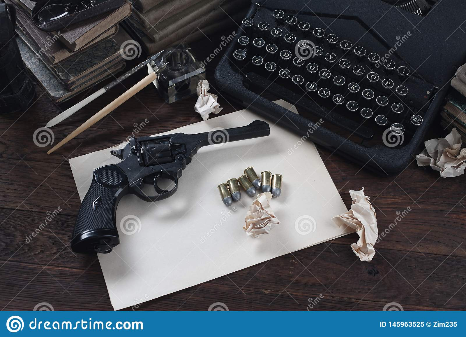 Scrivendo una storia di romanzo di crimine - vecchie retro macchina da scrivere e pistola d annata del revolver con le munizioni,