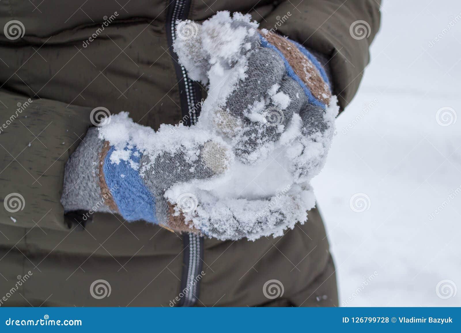 A sculpts a snowball,a woman wearing gloves takes snow