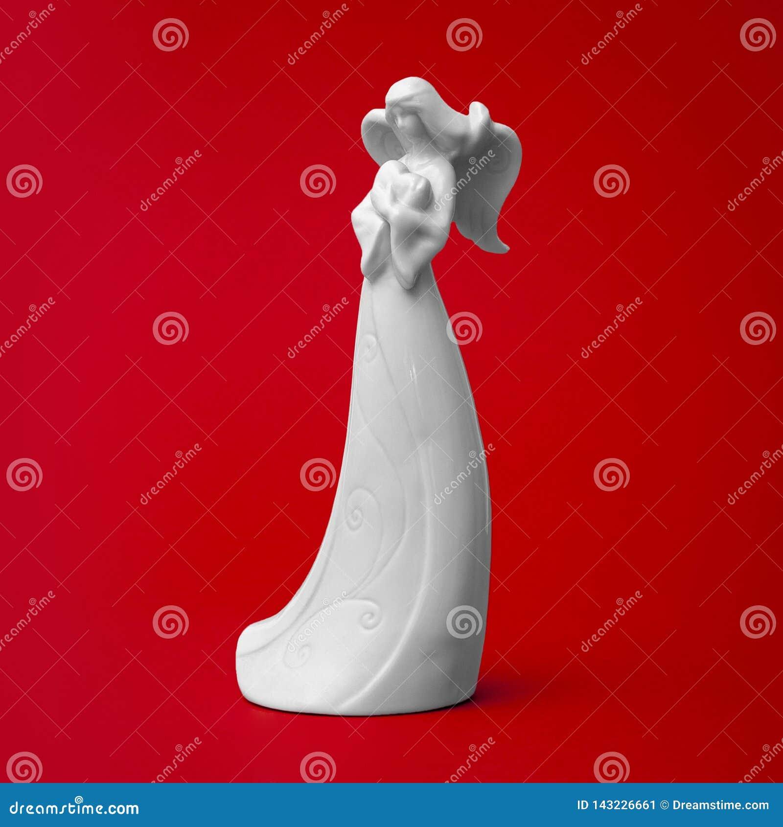 Sculpture blanche en ange de porcelaine avec le coeur dans des mains
