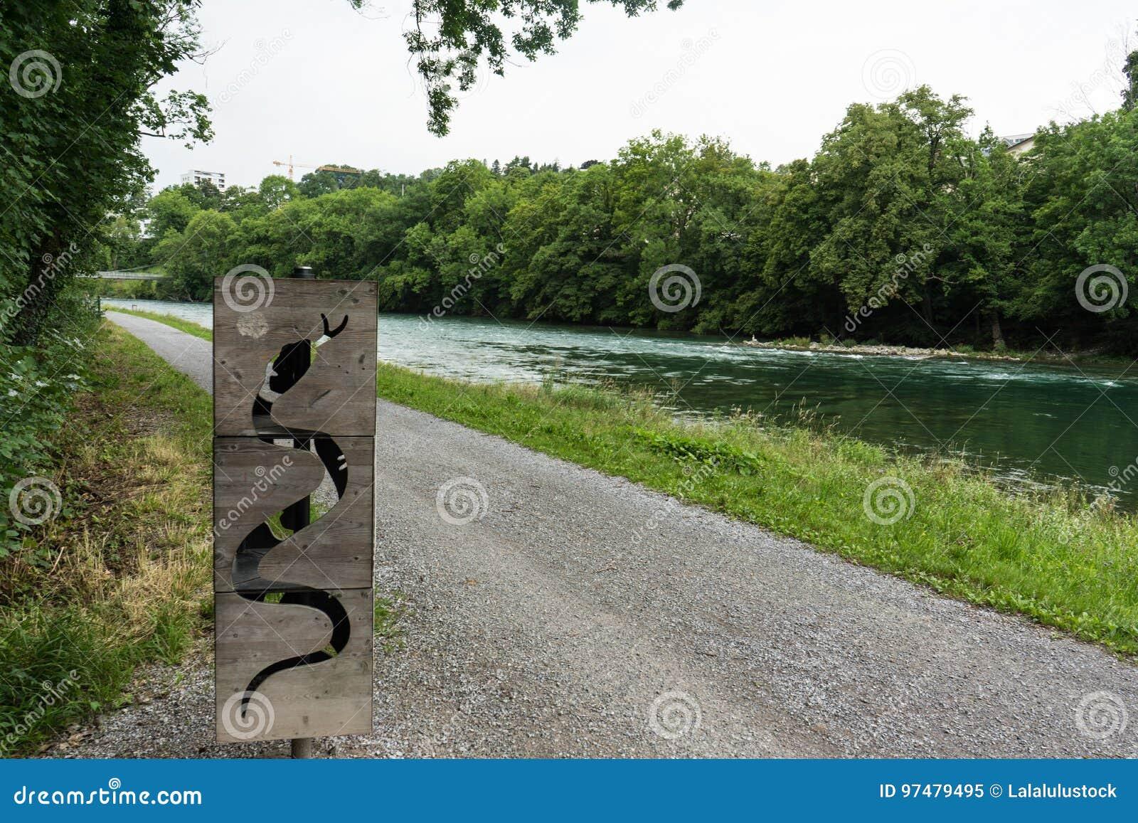 Sculpture en bois en serpent devant la rivière
