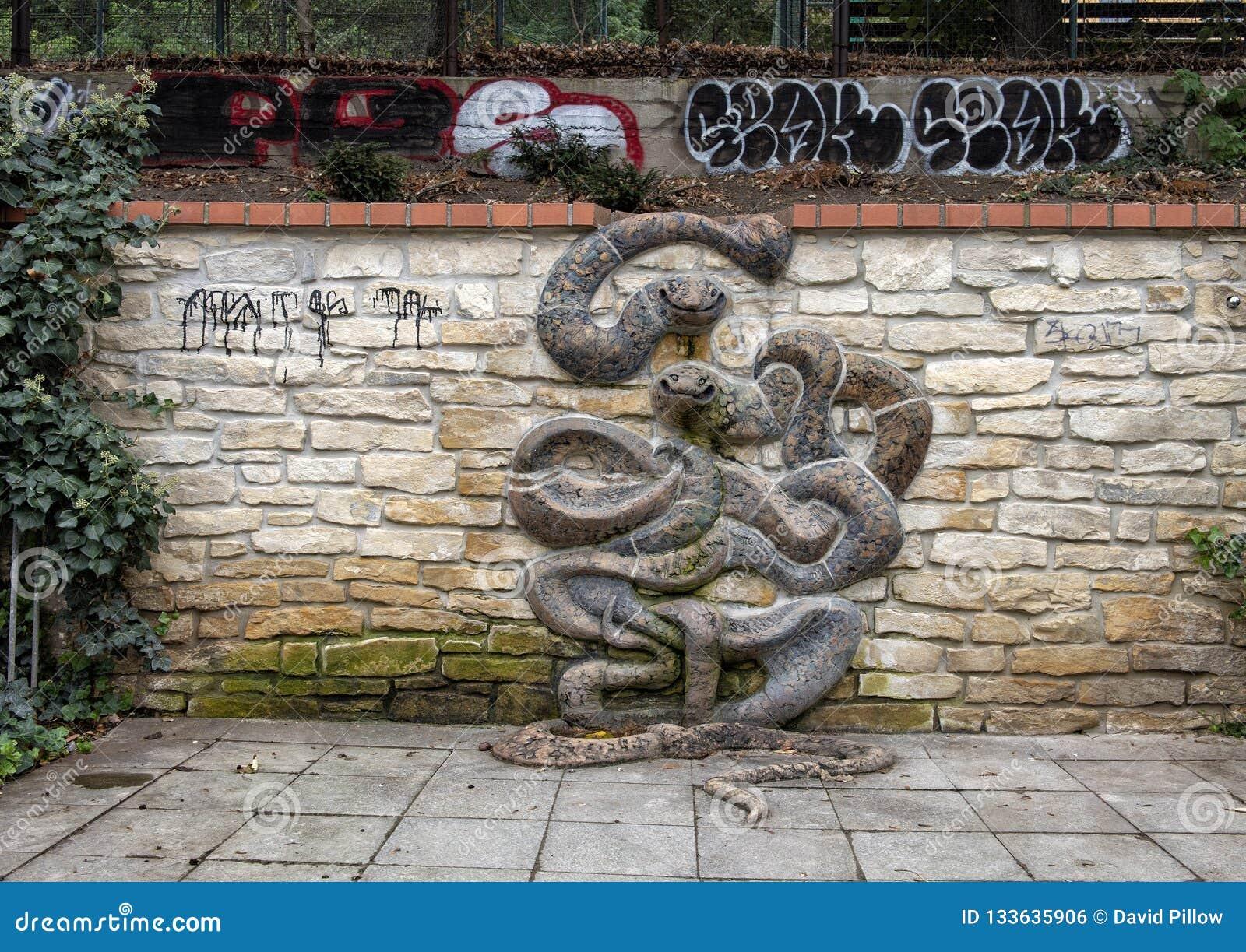 Sculpture en serpent sur le mur en pierre, avec le graffiti à l arrière-plan, Lesser Town, Prague, République Tchèque