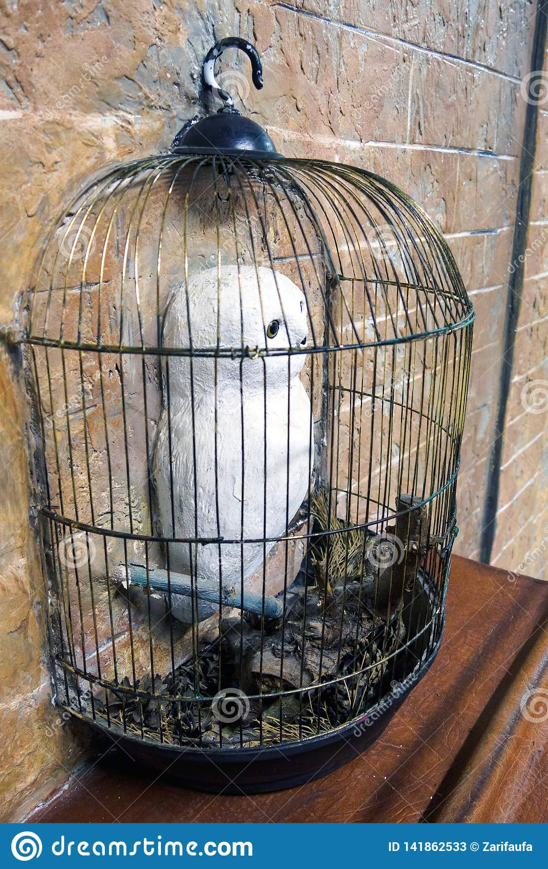 Sculpture of Harry Potter snowy owl in cage in wall