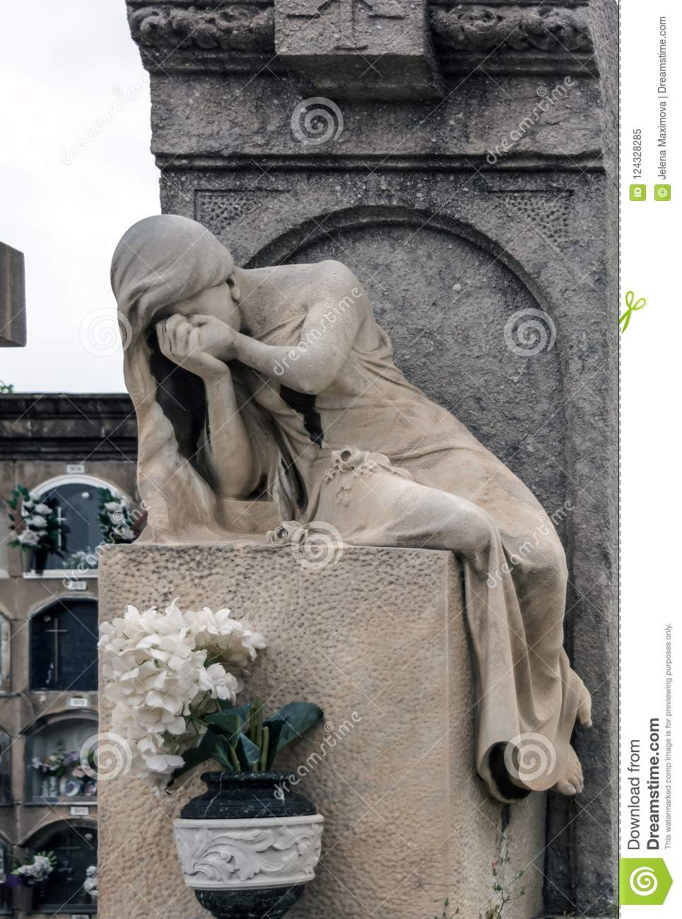 Sculpture of mourning crying woman on a grave
