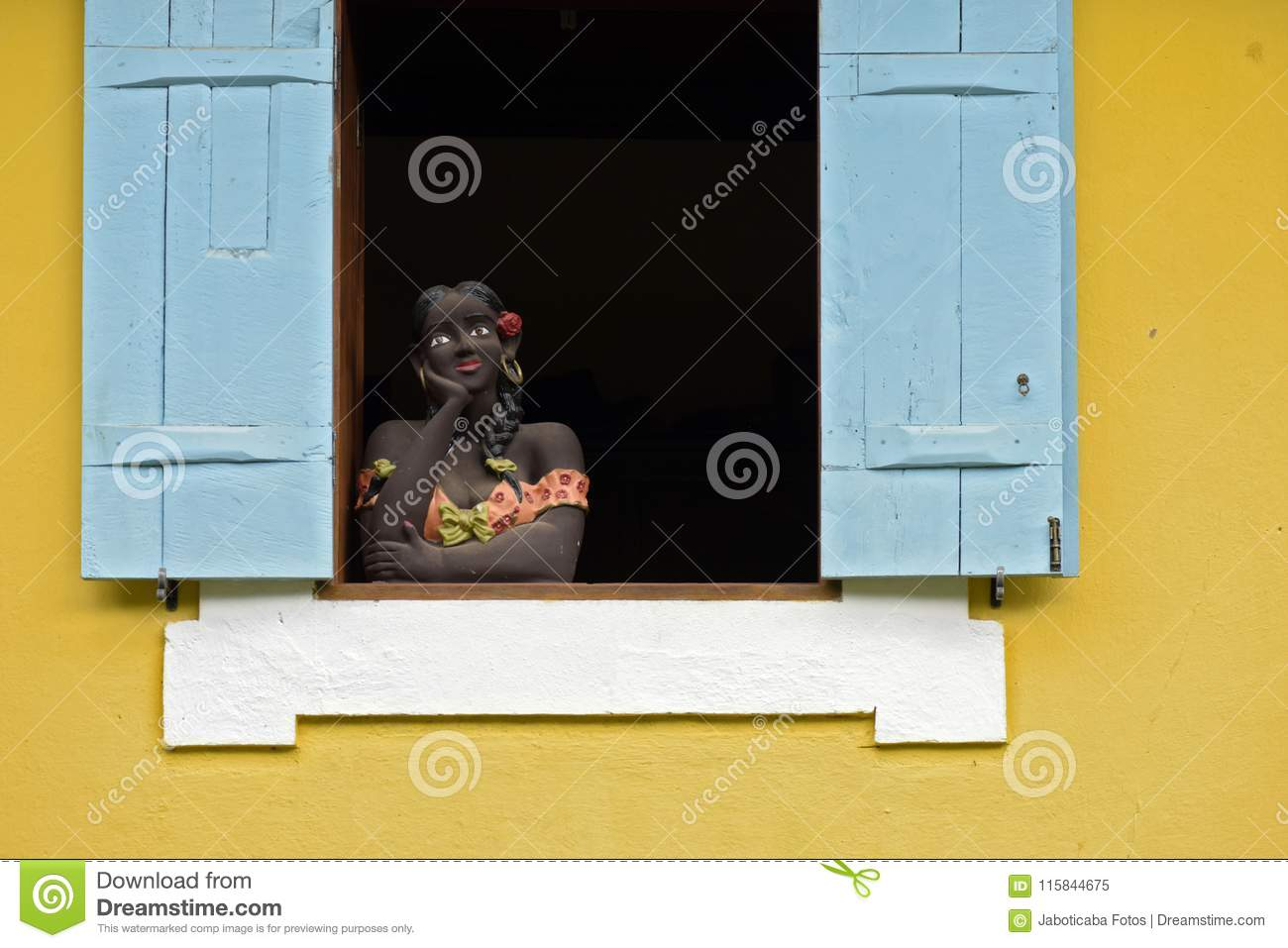 Sculpture of woman bust on blue window
