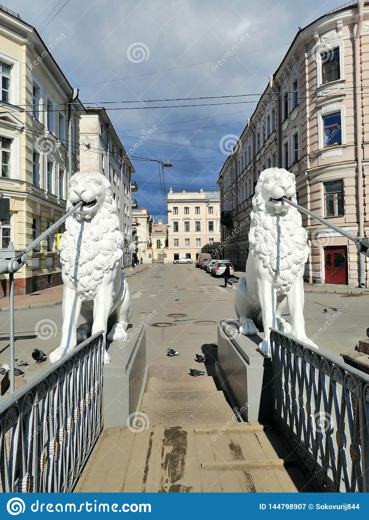 sculptures of lions holding the fence of the bridge
