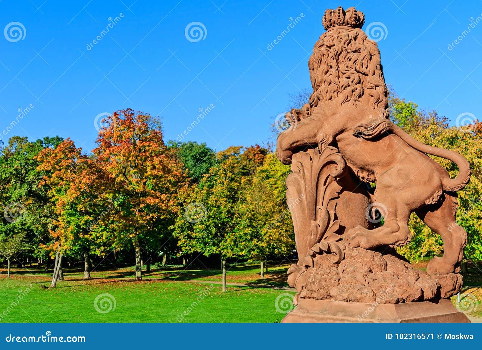 Scultura del leone in parco autunnale del castello di Phillipsruhe in Hanau, Germania