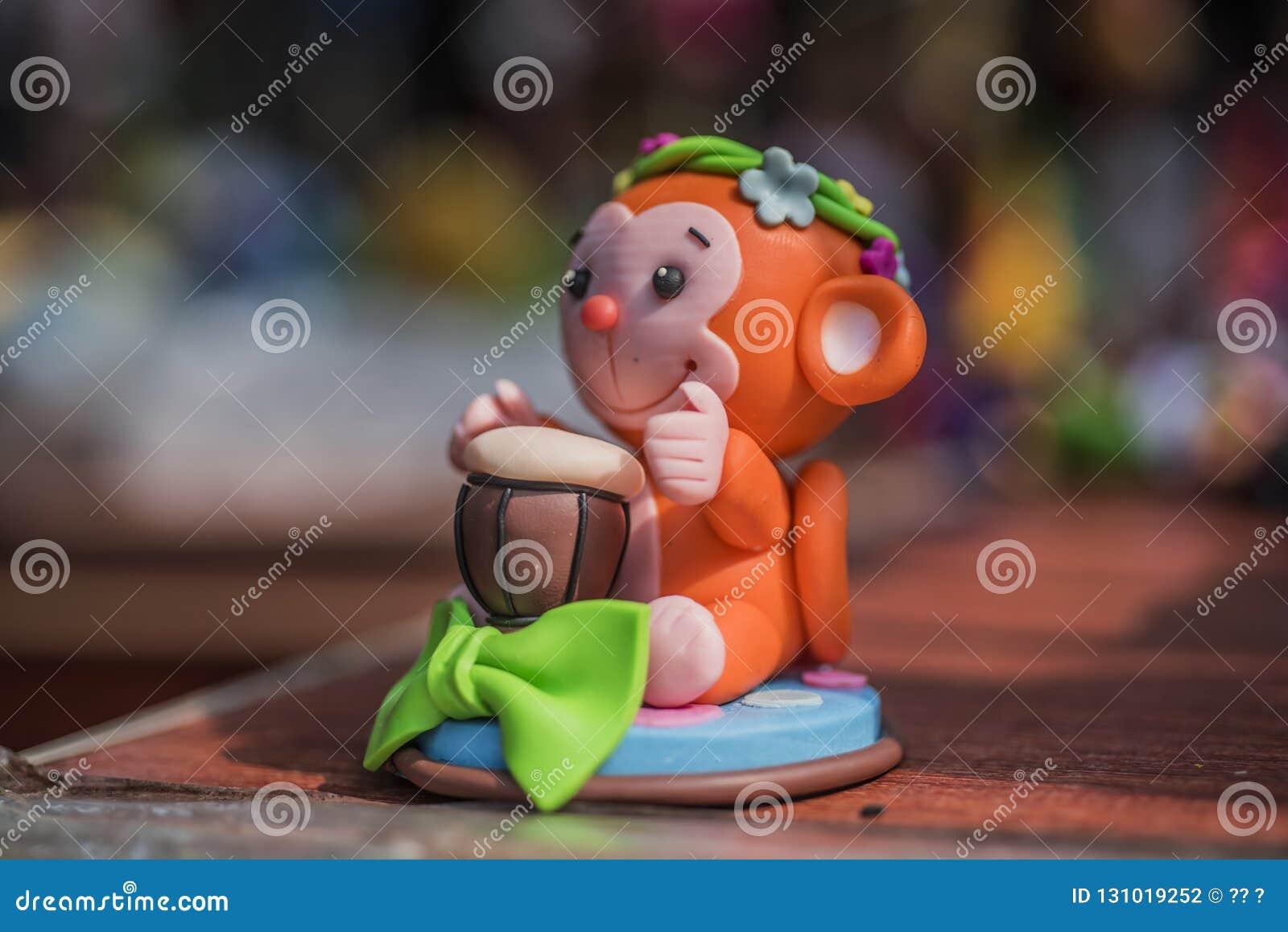 Scultura di argilla della scimmia rosso arancio che tamburella piccolo giocattolo