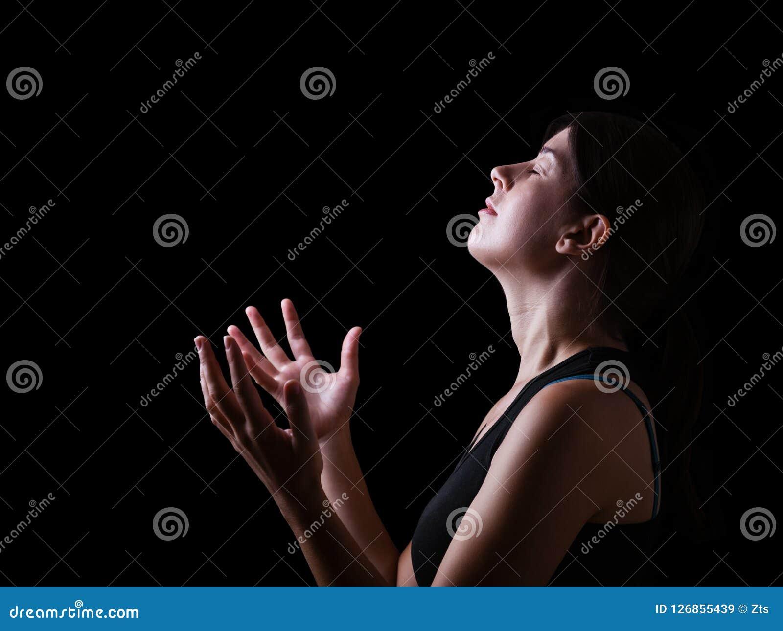 Scuro di una donna fedele che prega e che ritiene la presenza o essendo toccando dal dio