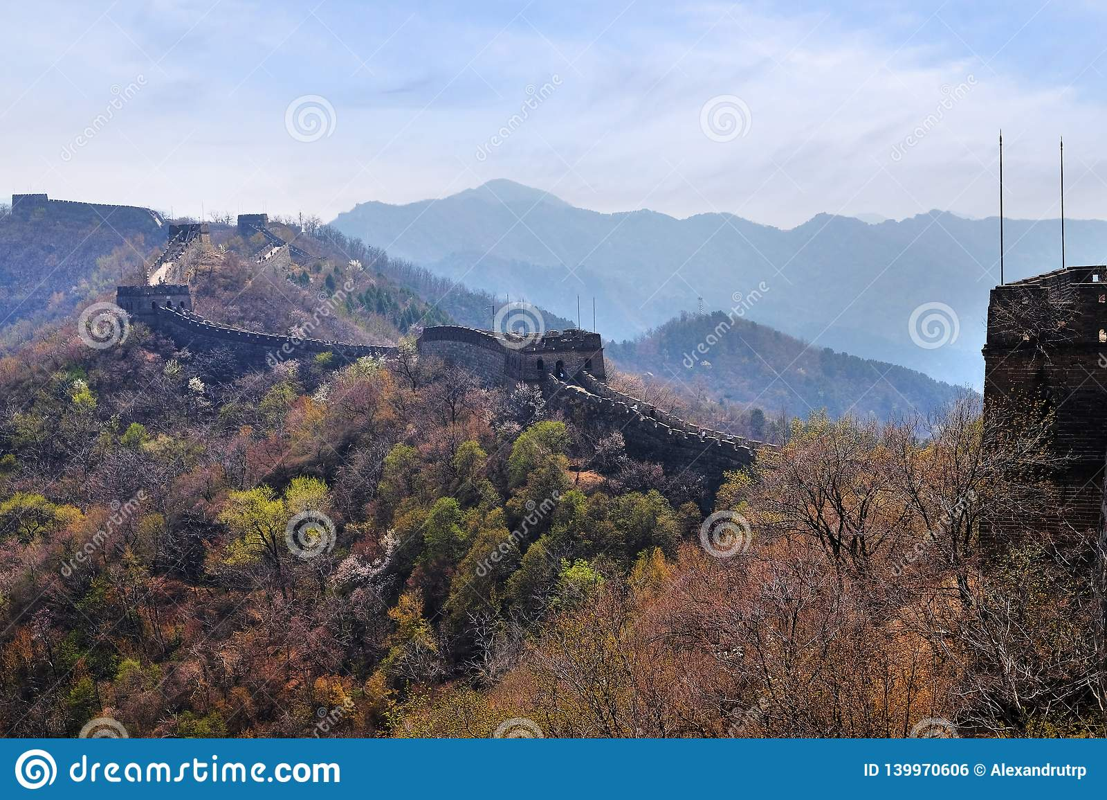 A seção de Mutianyu do Grande Muralha de China em um dia de mola ensolarado, contra um céu azul