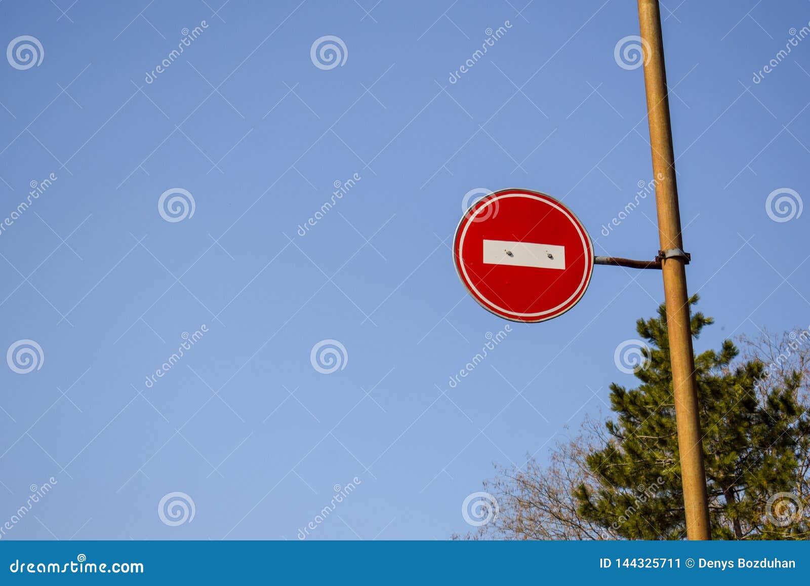 Señal de tráfico ninguna entrada contra el cielo azul y los árboles