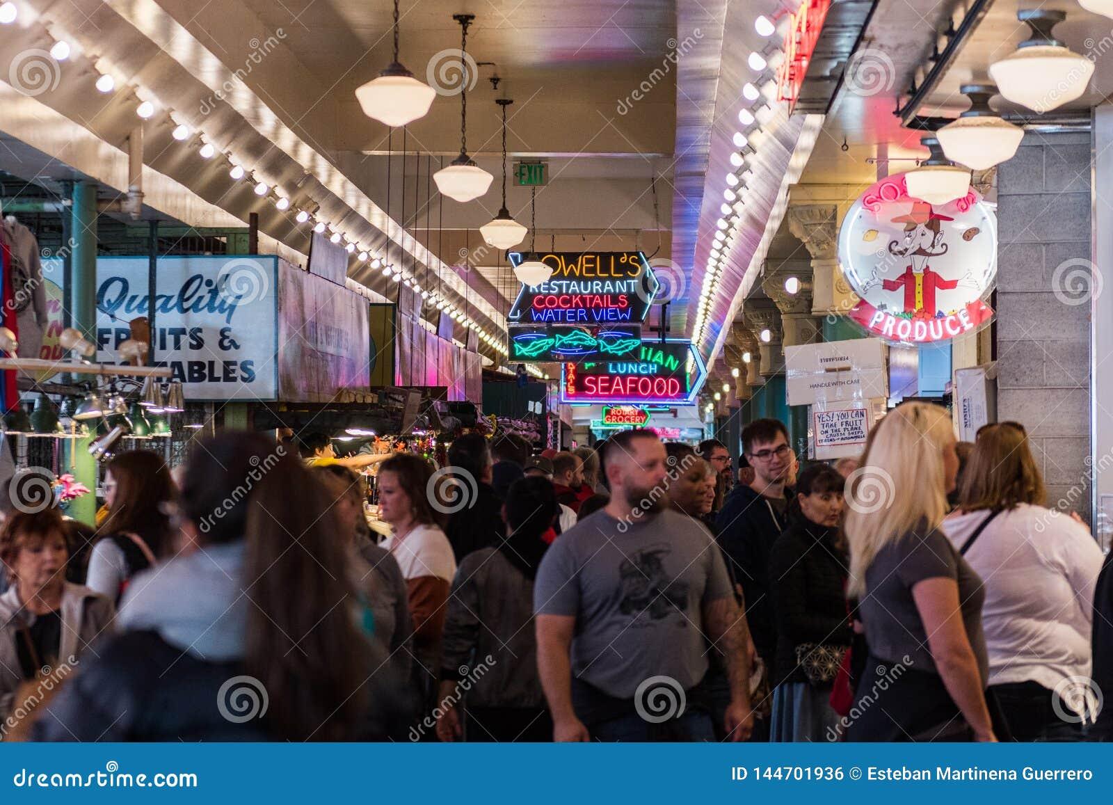 Señales de neón y gente dentro del mercado de Pike en Seattle, Washington, los E.E.U.U.