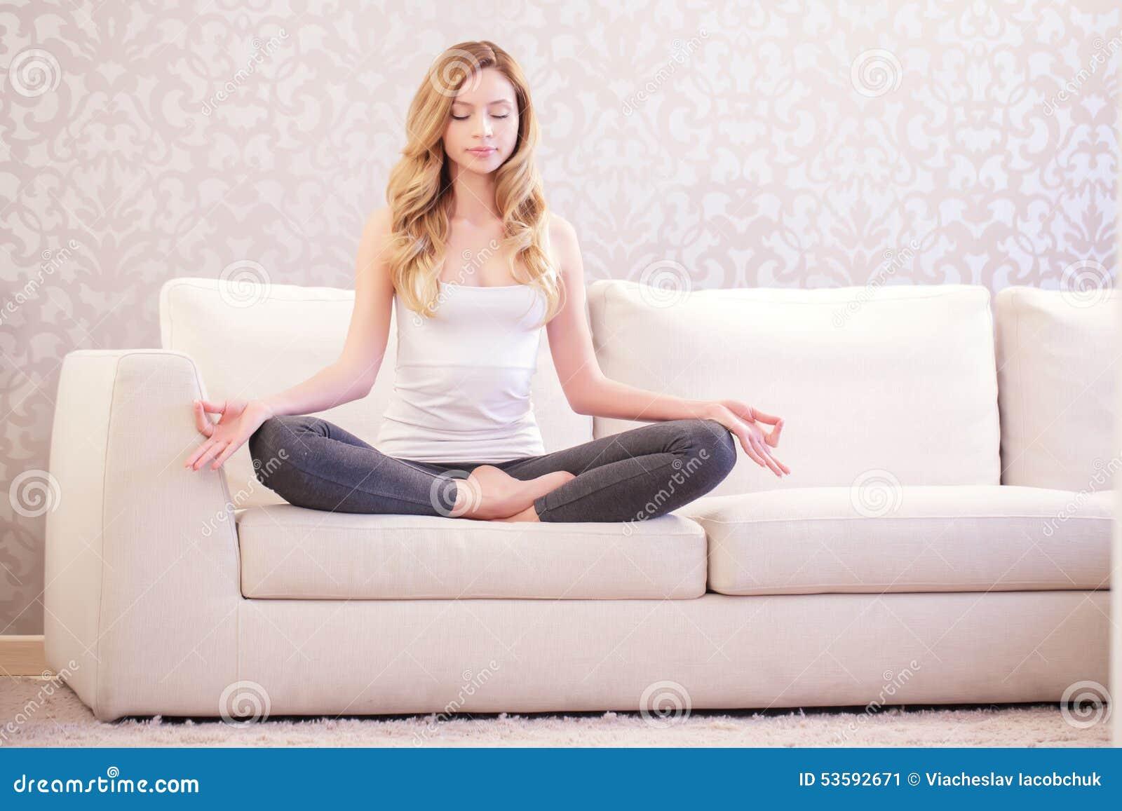 Señora bonita que hace yoga en el sofá
