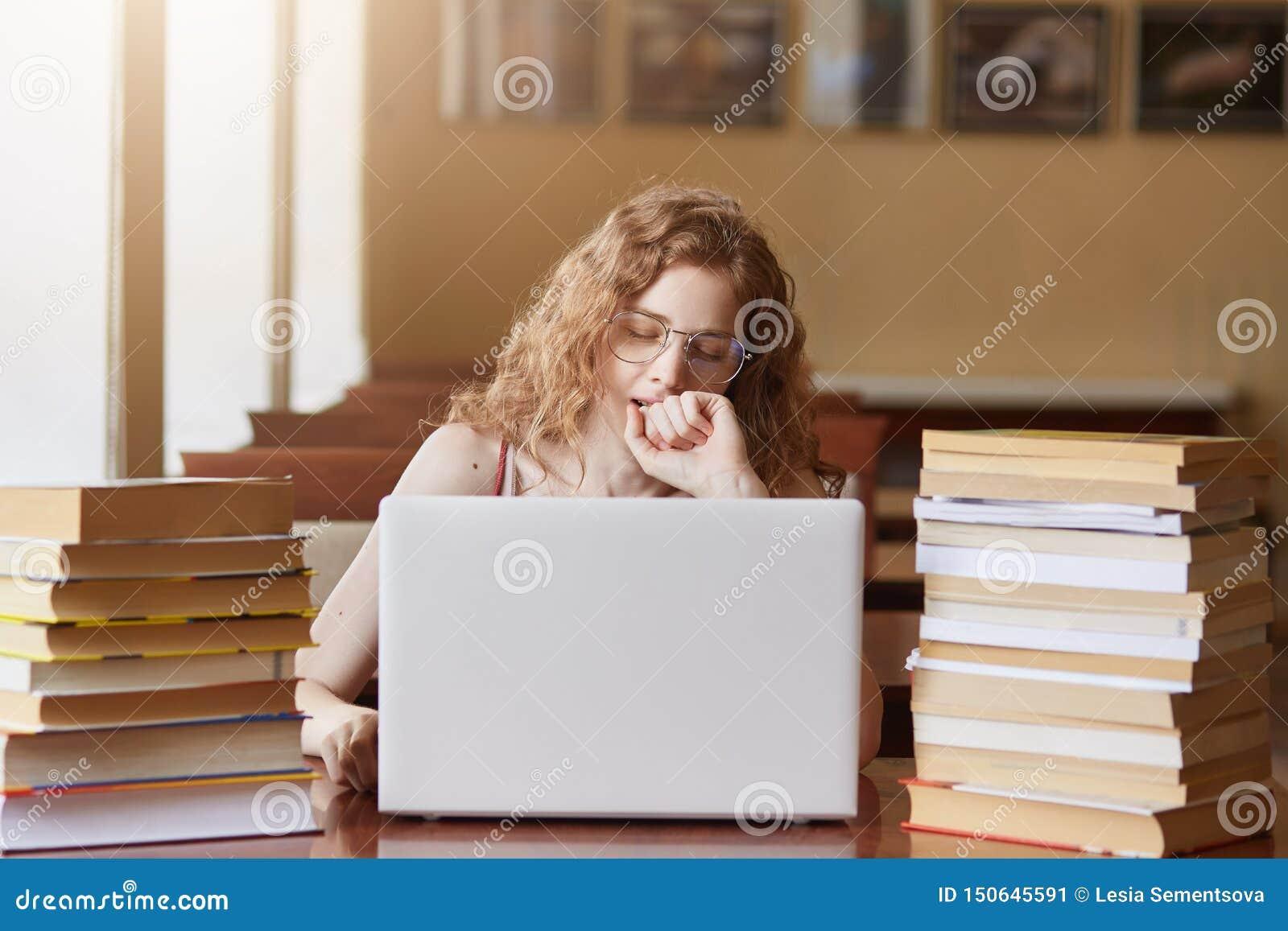Señora cansada agotada que se sienta en el escritorio en la biblioteca, cubriendo su boca con el puño mientras que bosteza, traba