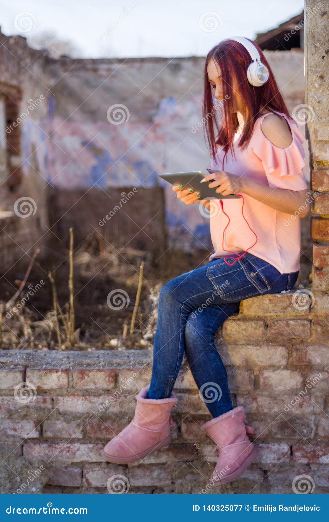 Señora de los pelirrojos con la tableta digital que escucha la música en los auriculares en ladrillos de la pared de las ruinas d