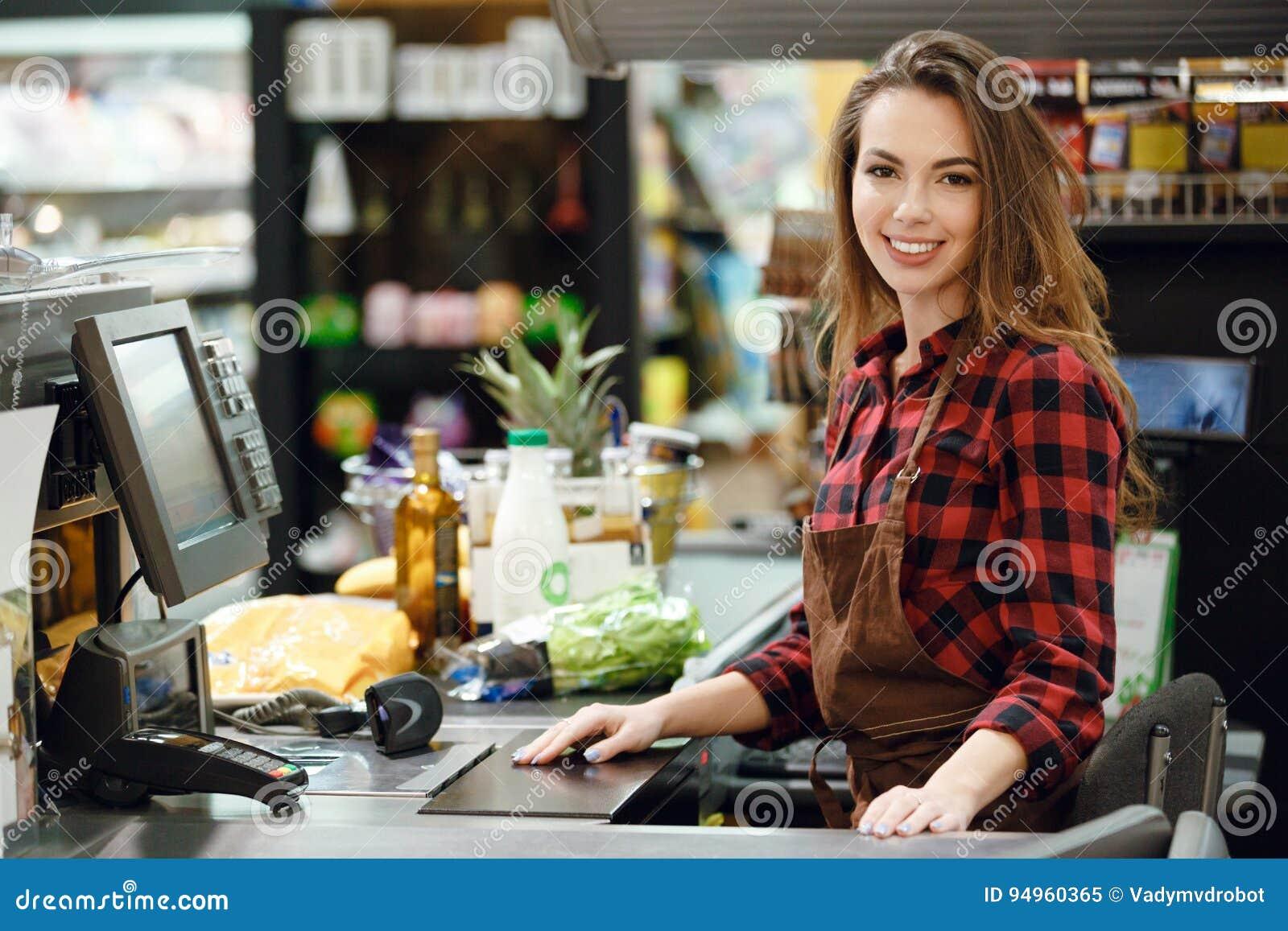 Señora del cajero en espacio de trabajo en tienda del supermercado