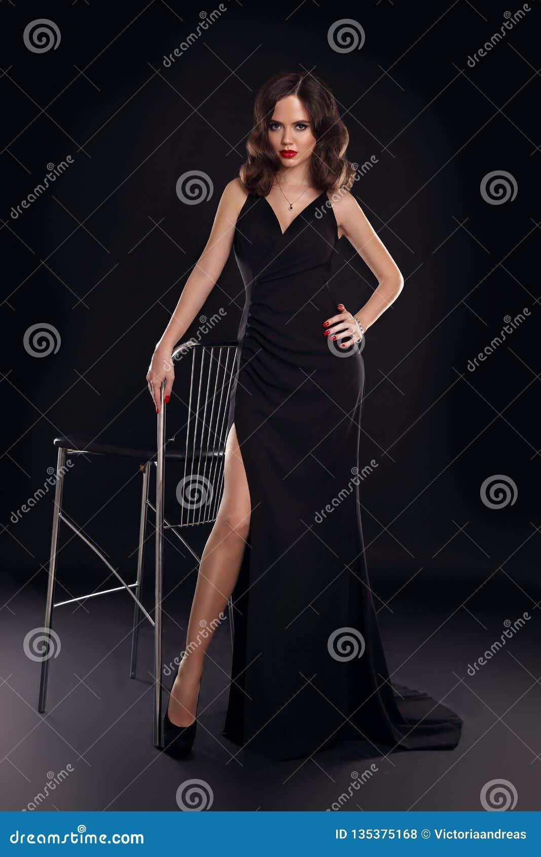 Señora elegante en el vestido sexy largo con la presentación ondulada retra del peinado aislado en fondo del negro del estudio Mu