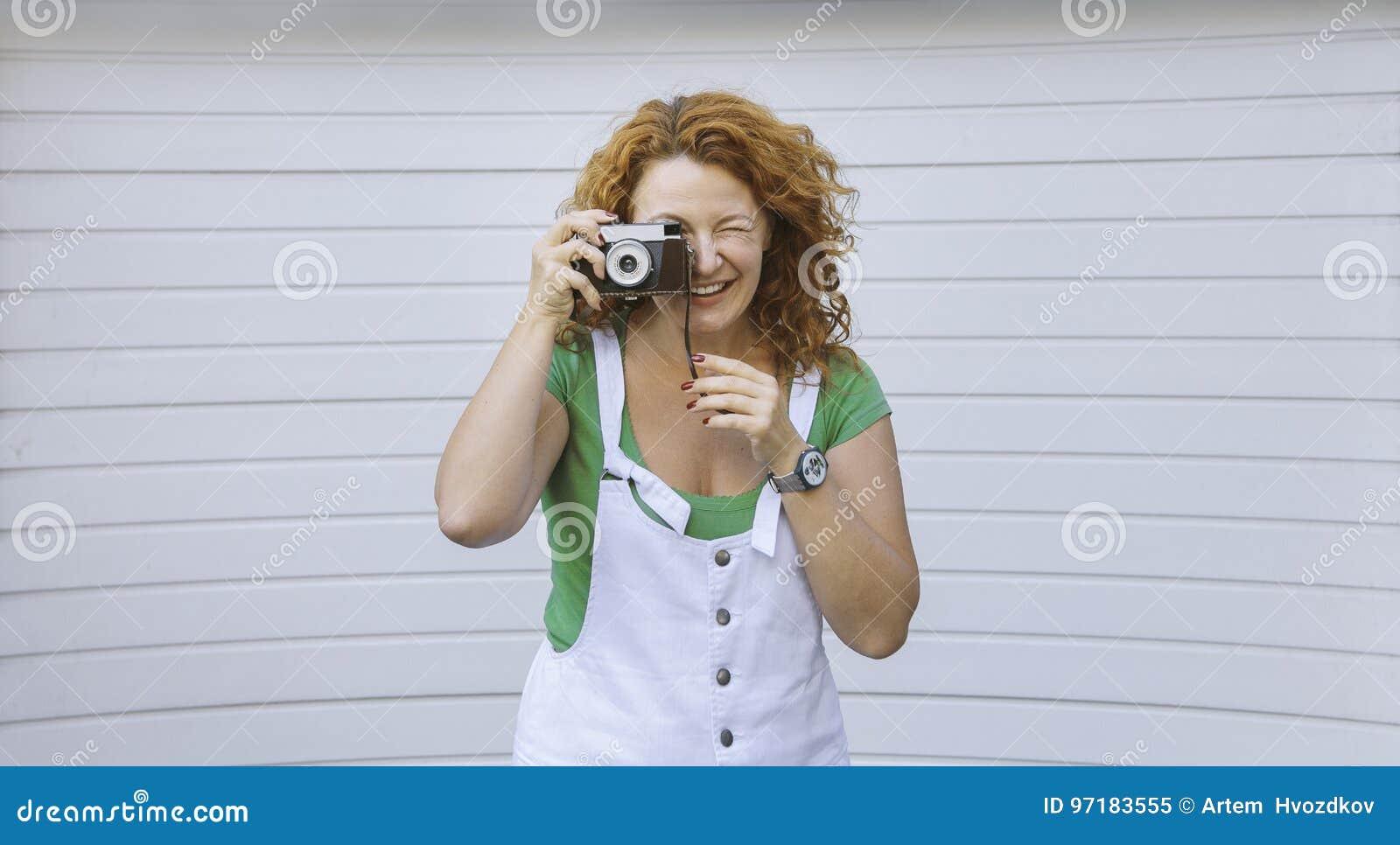 Señora envejecida centro alegre que usa la cámara del vintage Día, al aire libre Mujer roja feliz del pelo que toma la imagen en
