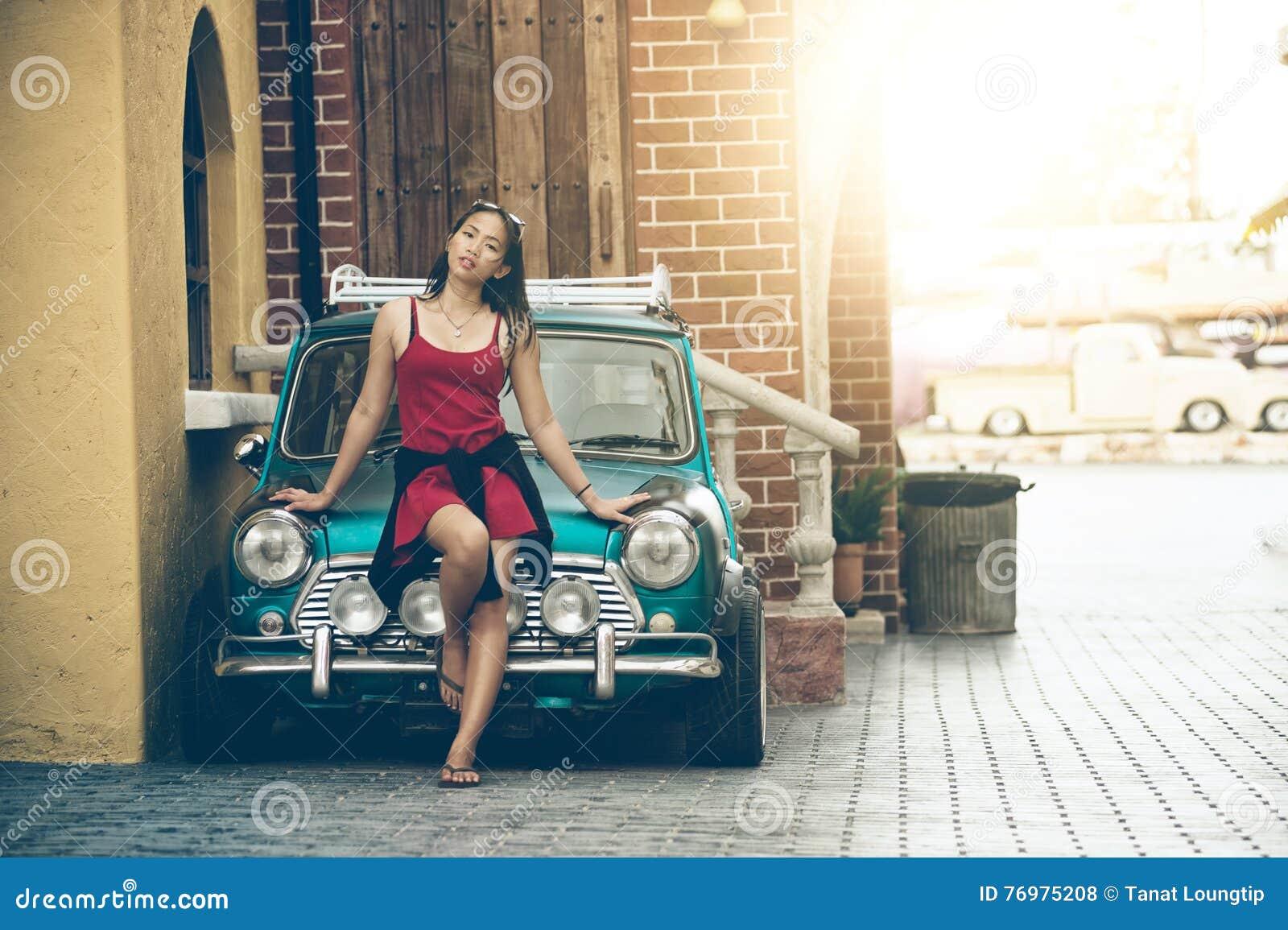 Señora hermosa de Asia que se coloca cerca del coche retro