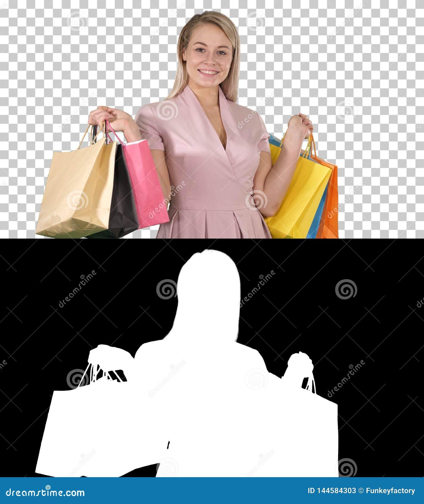 Señora joven bonita emocionada que se coloca de mirada de la cámara que muestra los bolsos de compras, Alpha Channel
