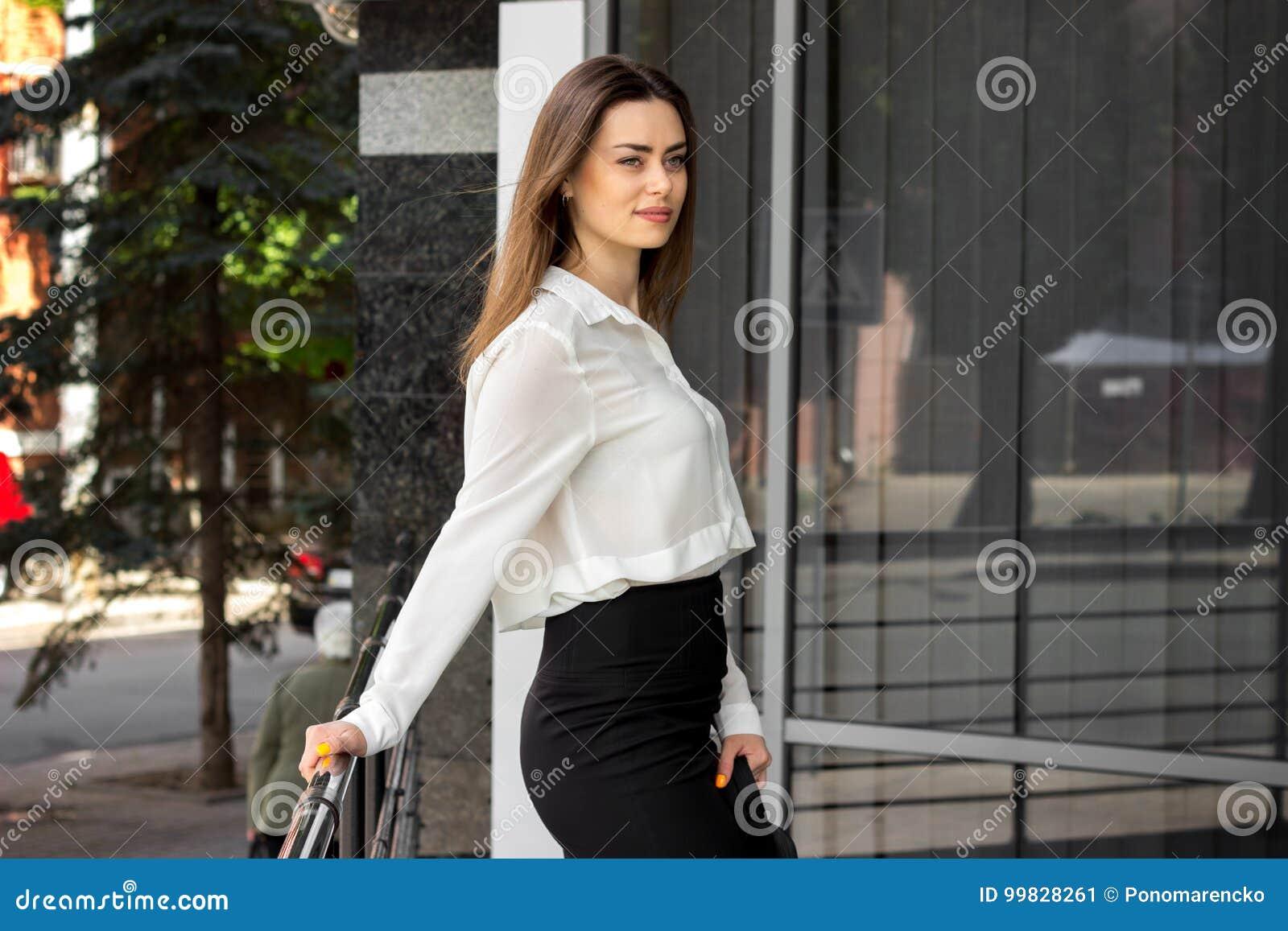 91ae1ceac4 La señora joven delgada hermosa en una camisa blanca y una falda negra se  coloca en la calle