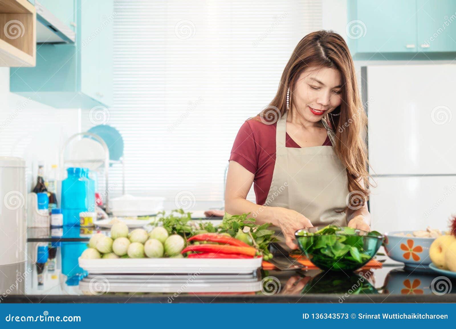 Señora joven en cocina brillante moderna preparar la comida