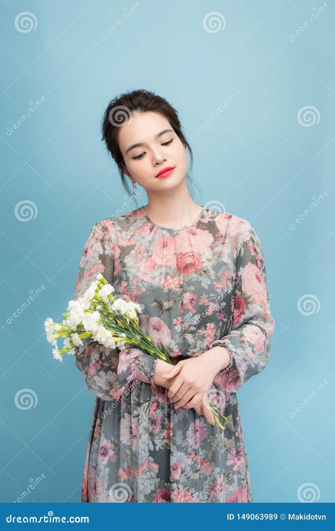 Se?ora joven hermosa con el vestido lindo en fondo azul