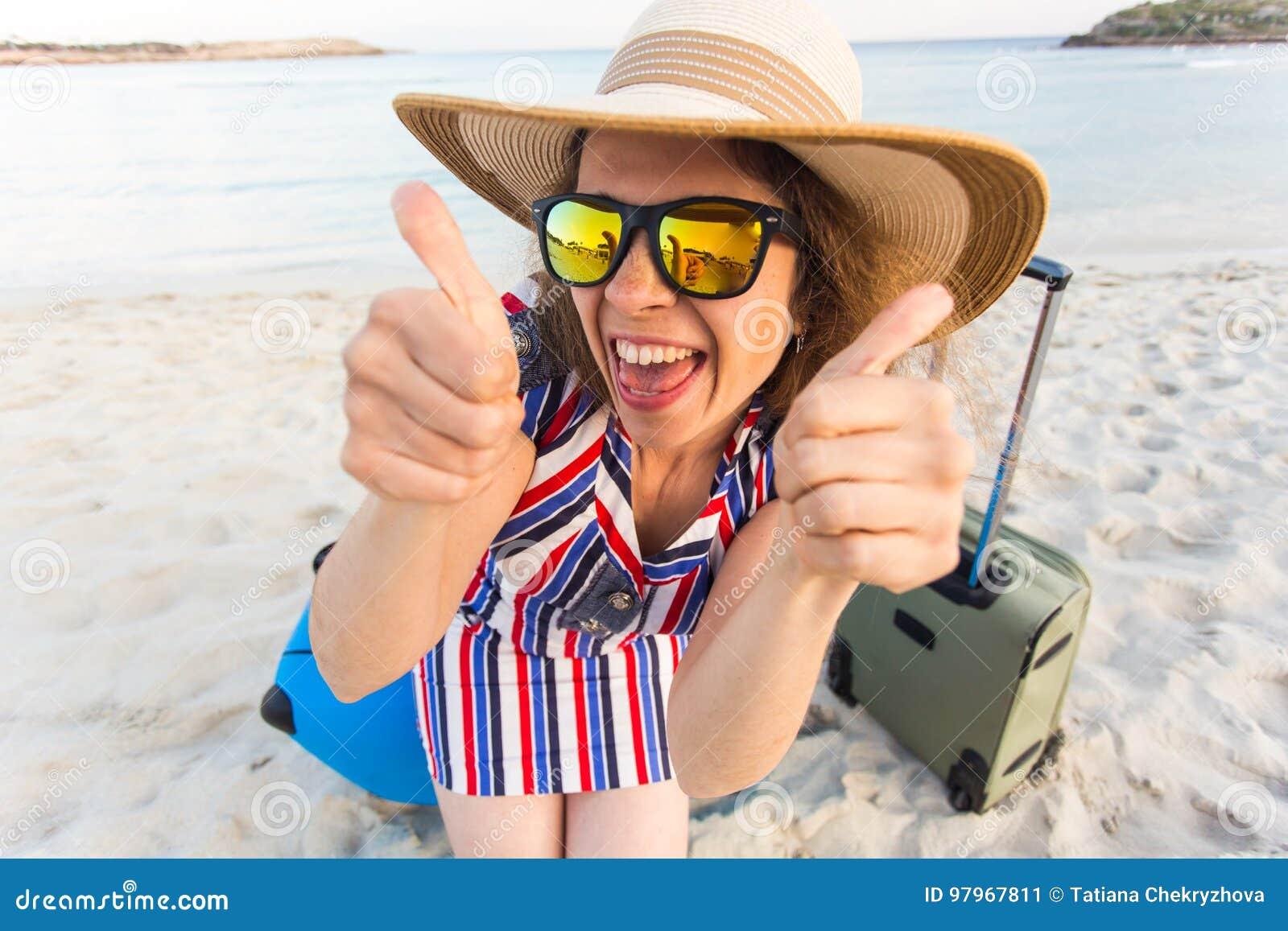 Señora joven hermosa con una maleta azul que muestra los pulgares encima del gesto en la playa Gente, viaje, vacaciones y verano