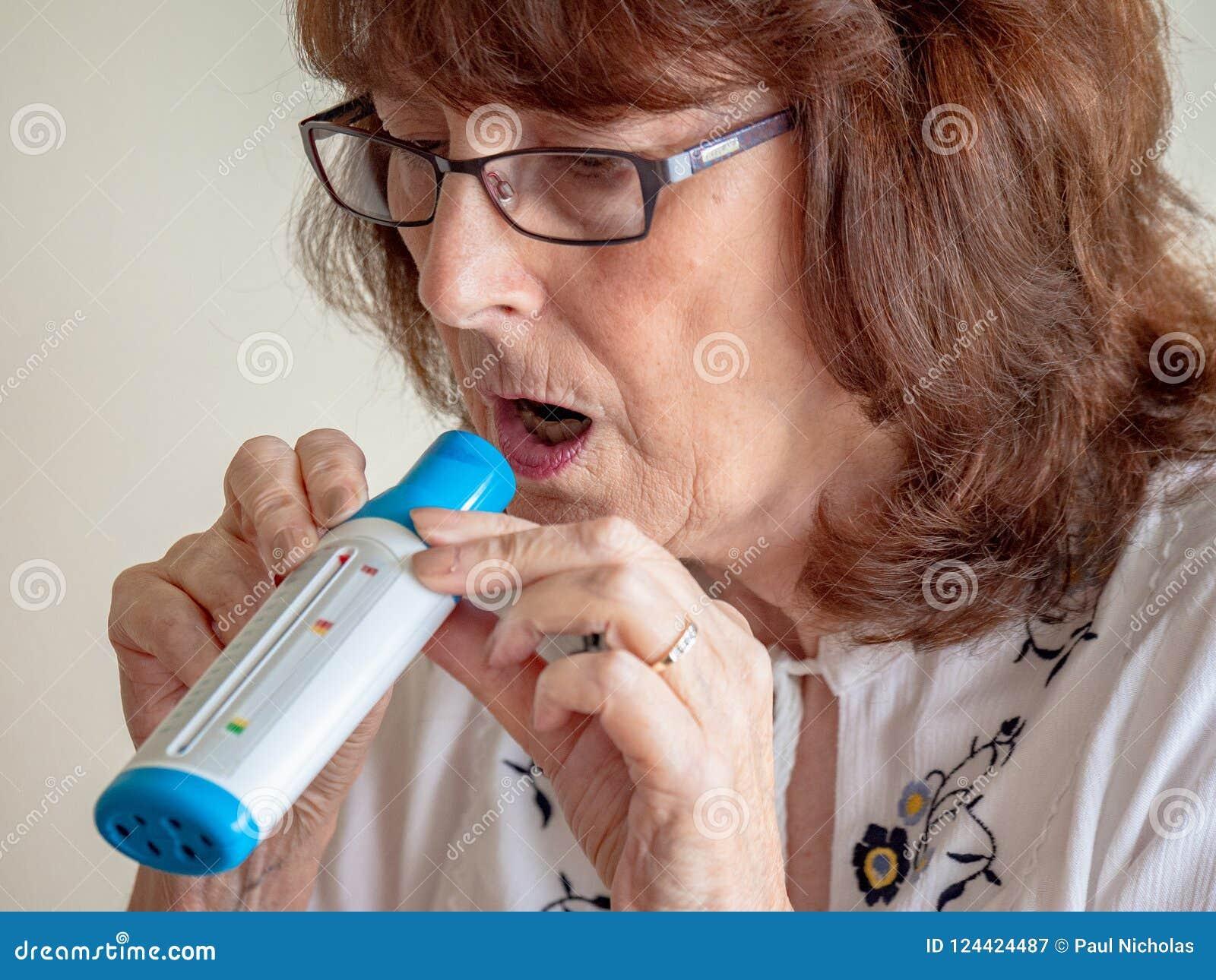 Señora madura que usa el monitor del flujo de aire del pulmón