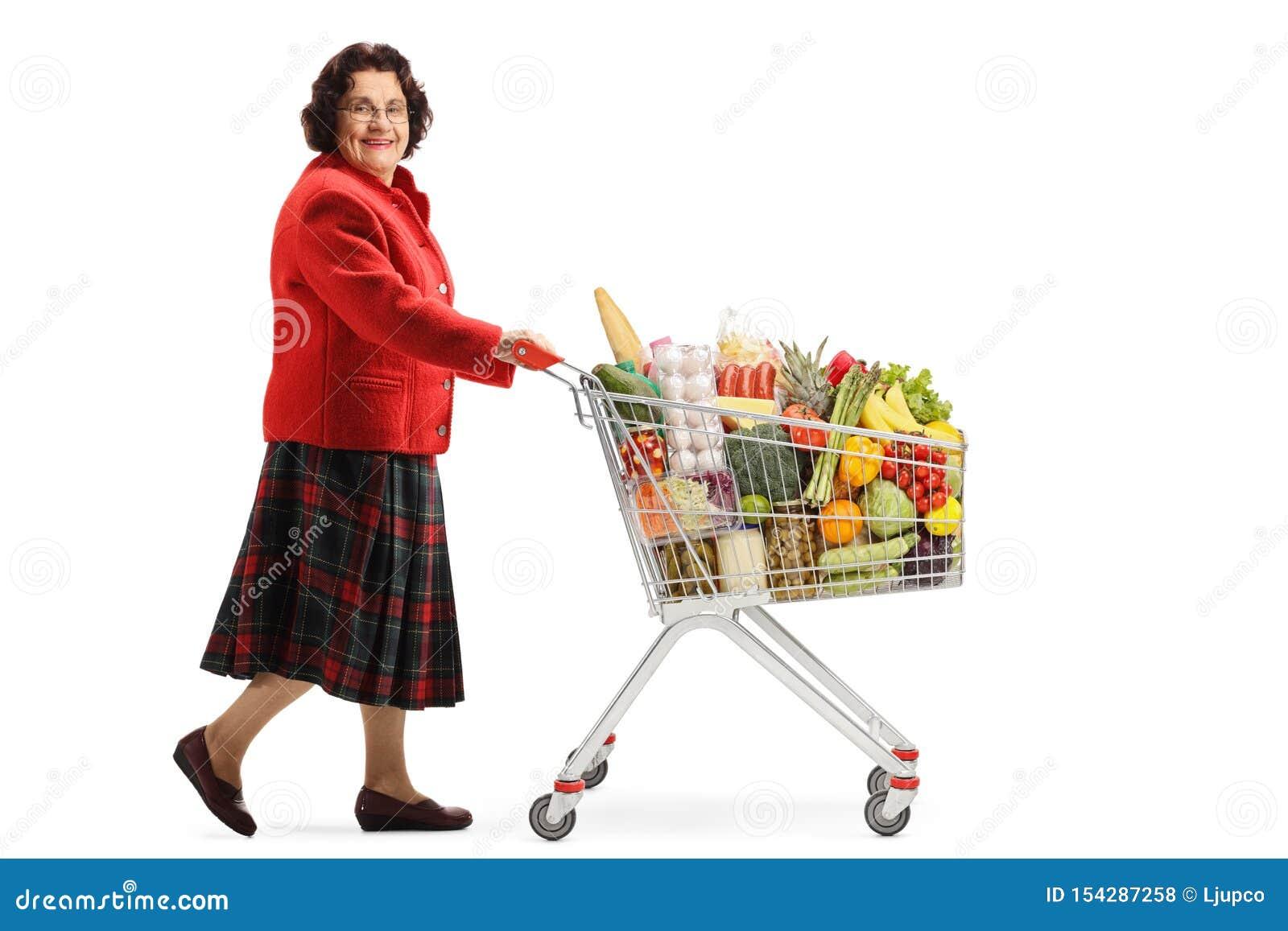 Señora mayor que camina con un carro de la compra con la comida y que sonríe en la cámara