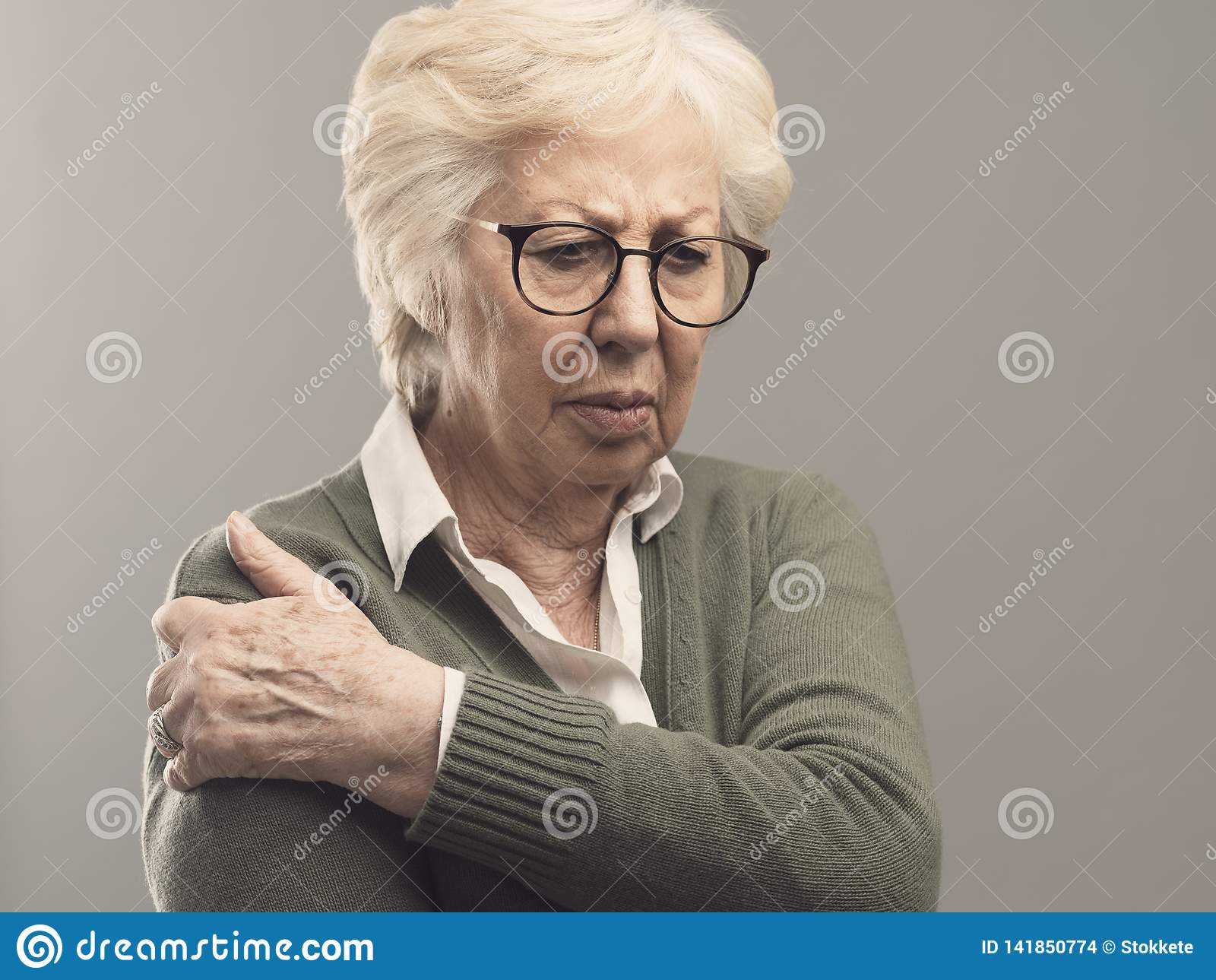 Señora mayor triste con el brazo y el dolor común
