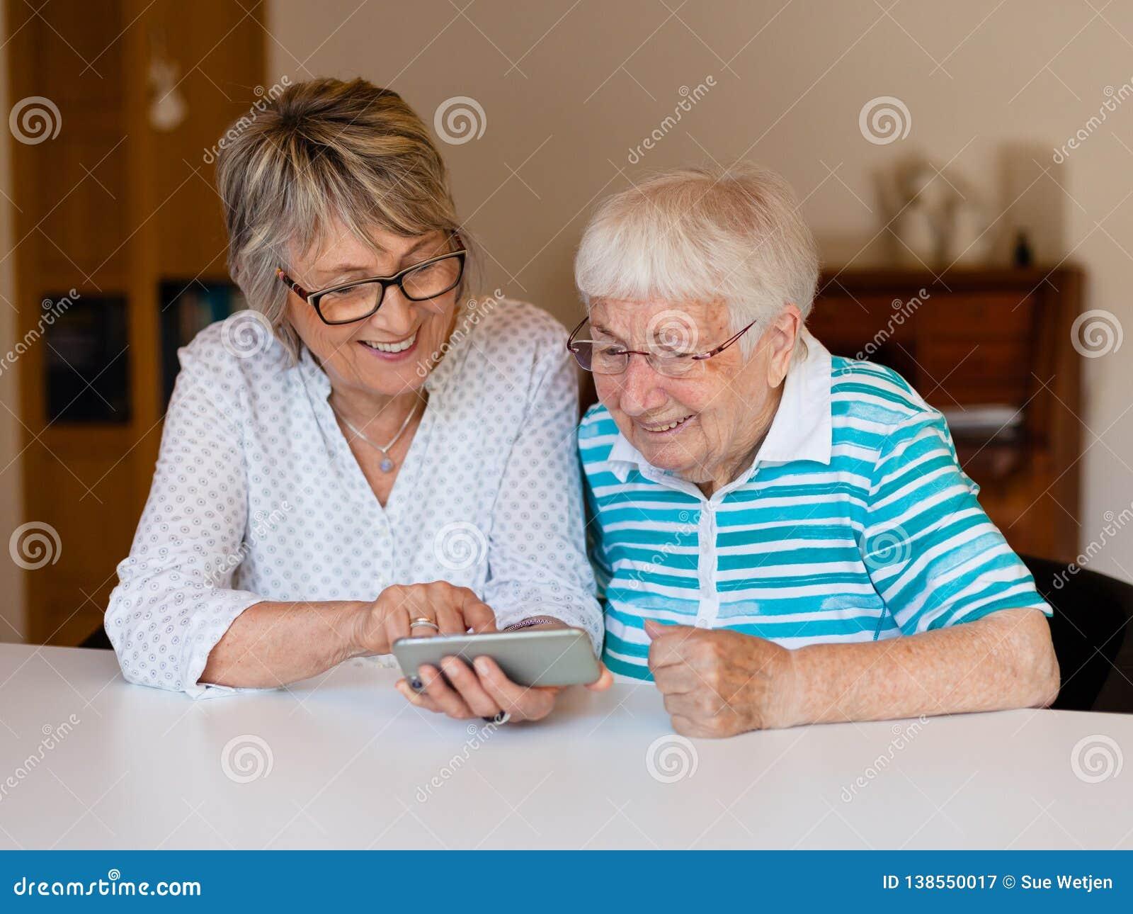 Señora mayor usando el teléfono elegante con su madre